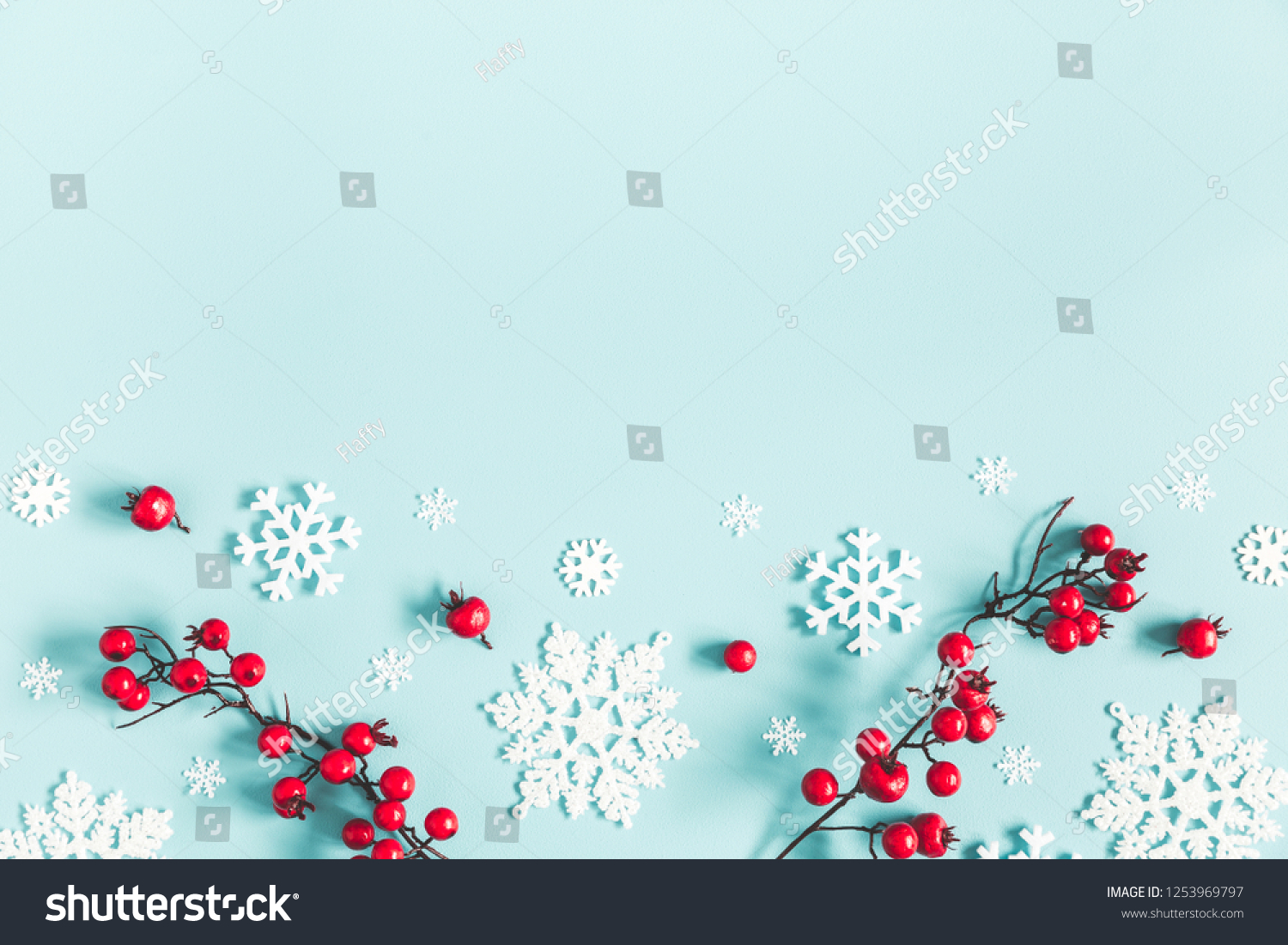 Christmas or winter composition. Frame made of snowflakes and red berries on pastel blue background. Christmas, winter, new year concept. Flat lay, top view, copy space #1253969797