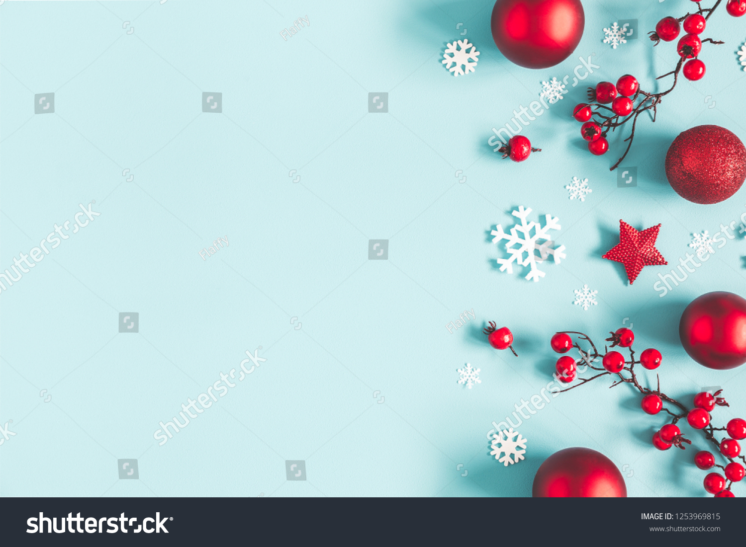 Christmas or winter composition. Frame made of snowflakes, balls and red berries on pastel blue background. Christmas, winter, new year concept. Flat lay, top view, copy space #1253969815