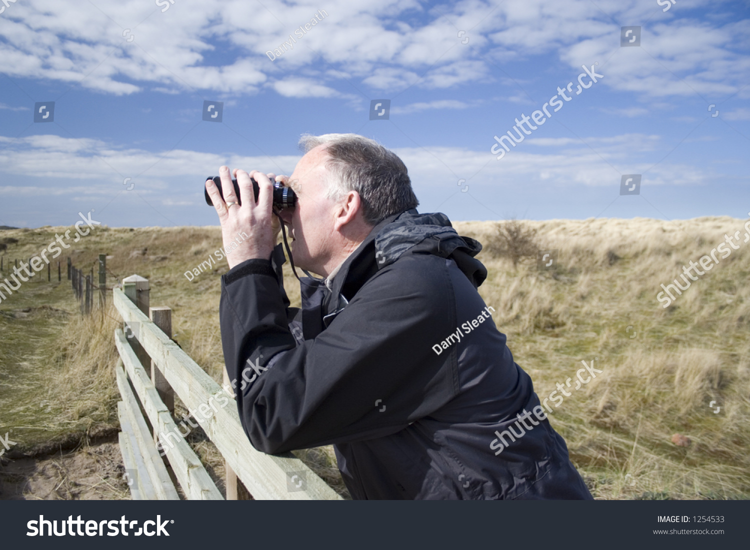 Man Resting On Fence Observing Wildlife With Binoculars ...