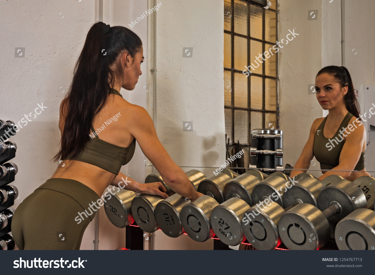 https://image.shutterstock.com/z/stock-photo-athletic-woman-takes-dumbbells-into-her-hand-in-front-of-the-mirror-1254767713.jpg