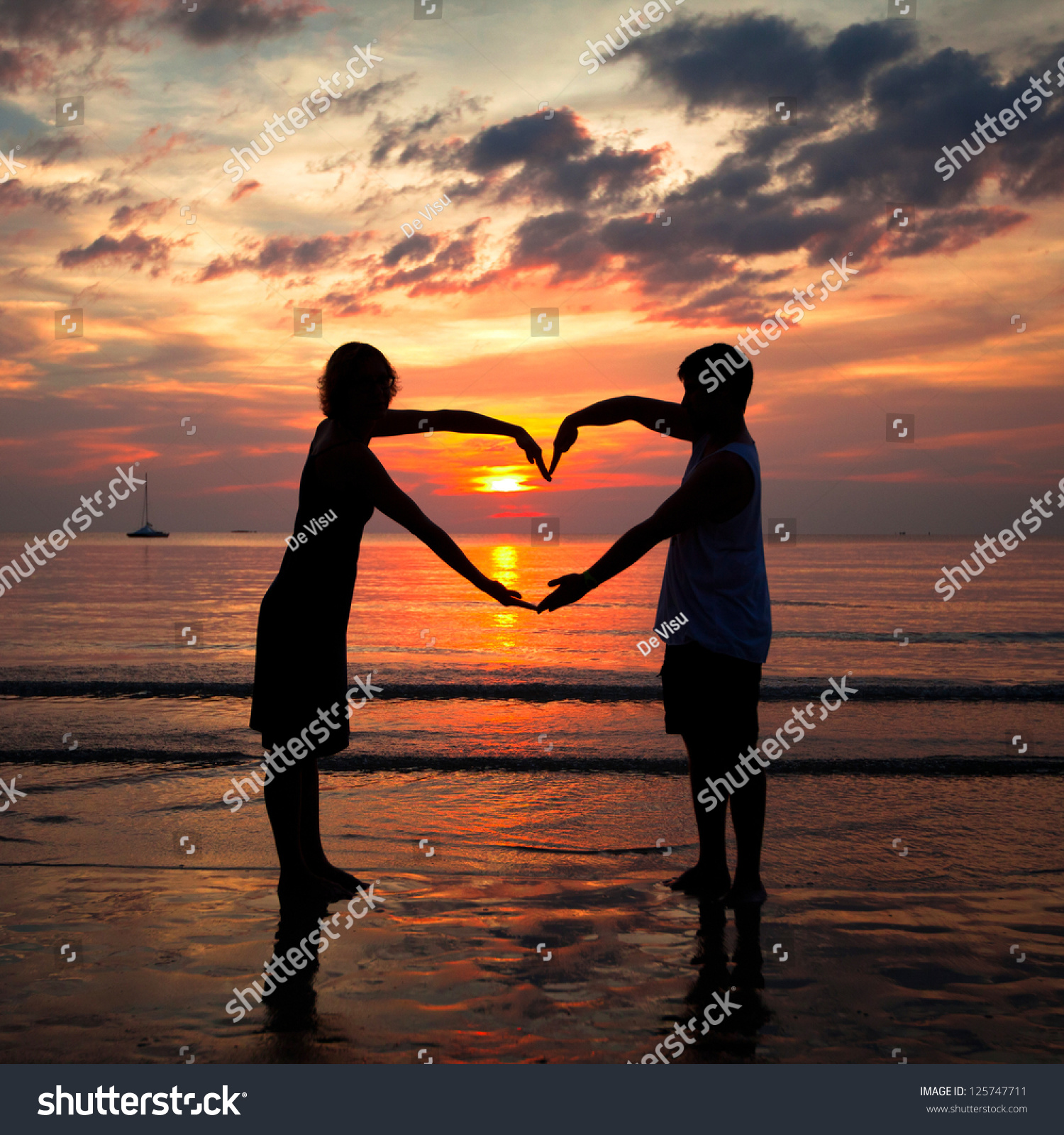 Young Couple Holding Hands Heart-Shaped On The Sea Beach