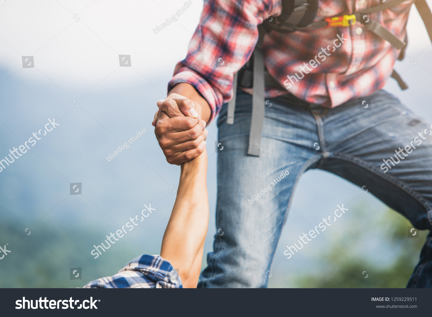 Helping hand outstretched for salvation . Strong hold. Couple hiking help each other in mountains . Two people climbing on mountain and helping. #1259229511