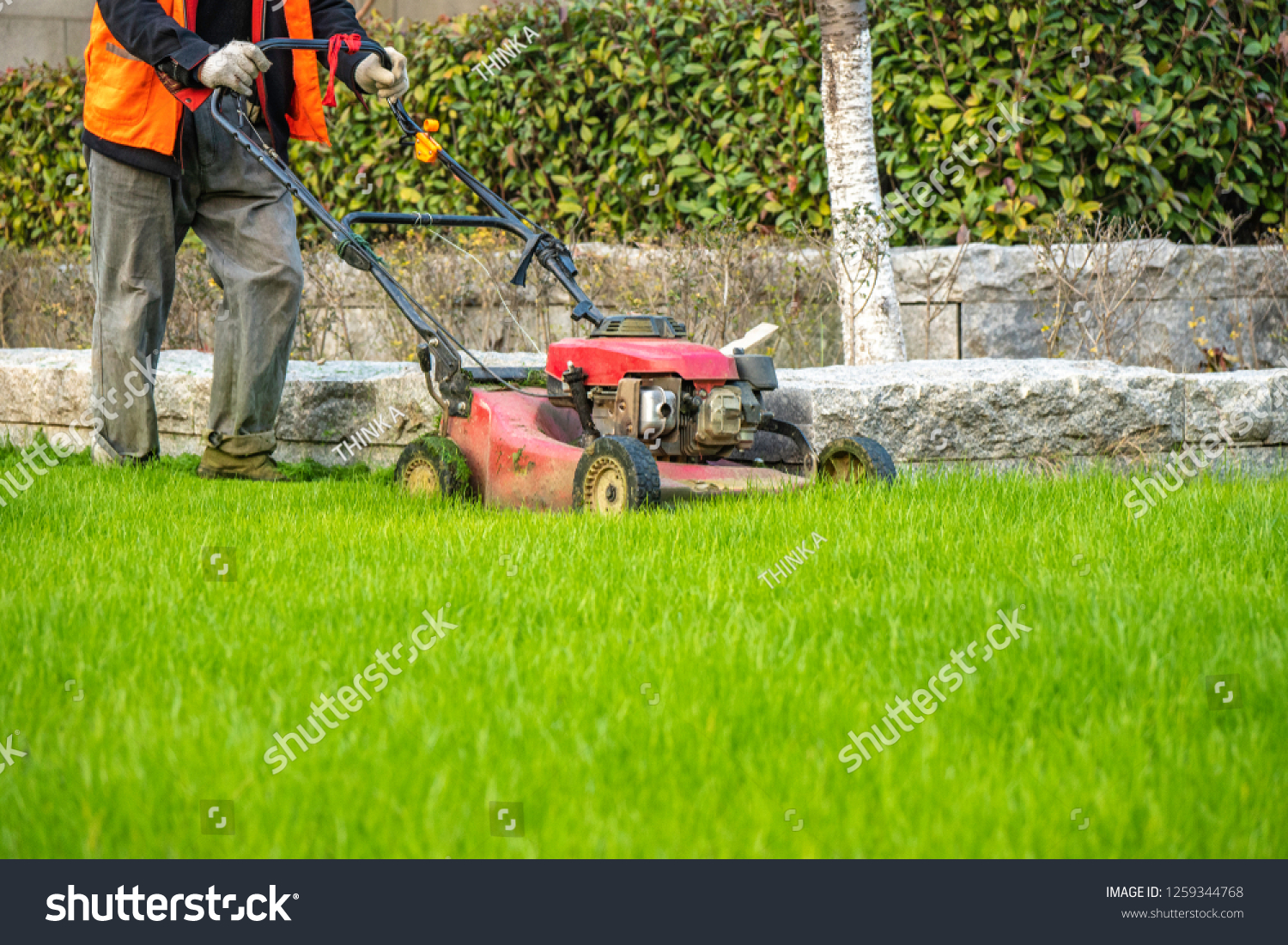 worker mowing lawns during sunset #1259344768