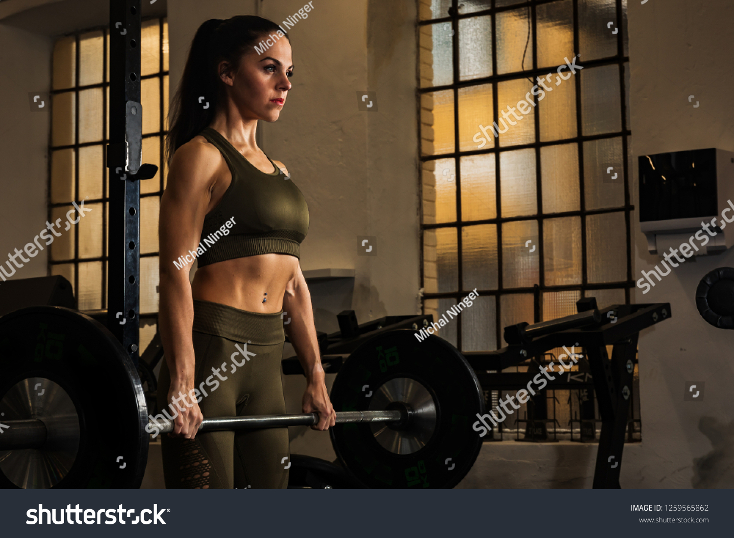 beautiful woman is workouting at the gym,  strengthens the barbell, lifting large weights