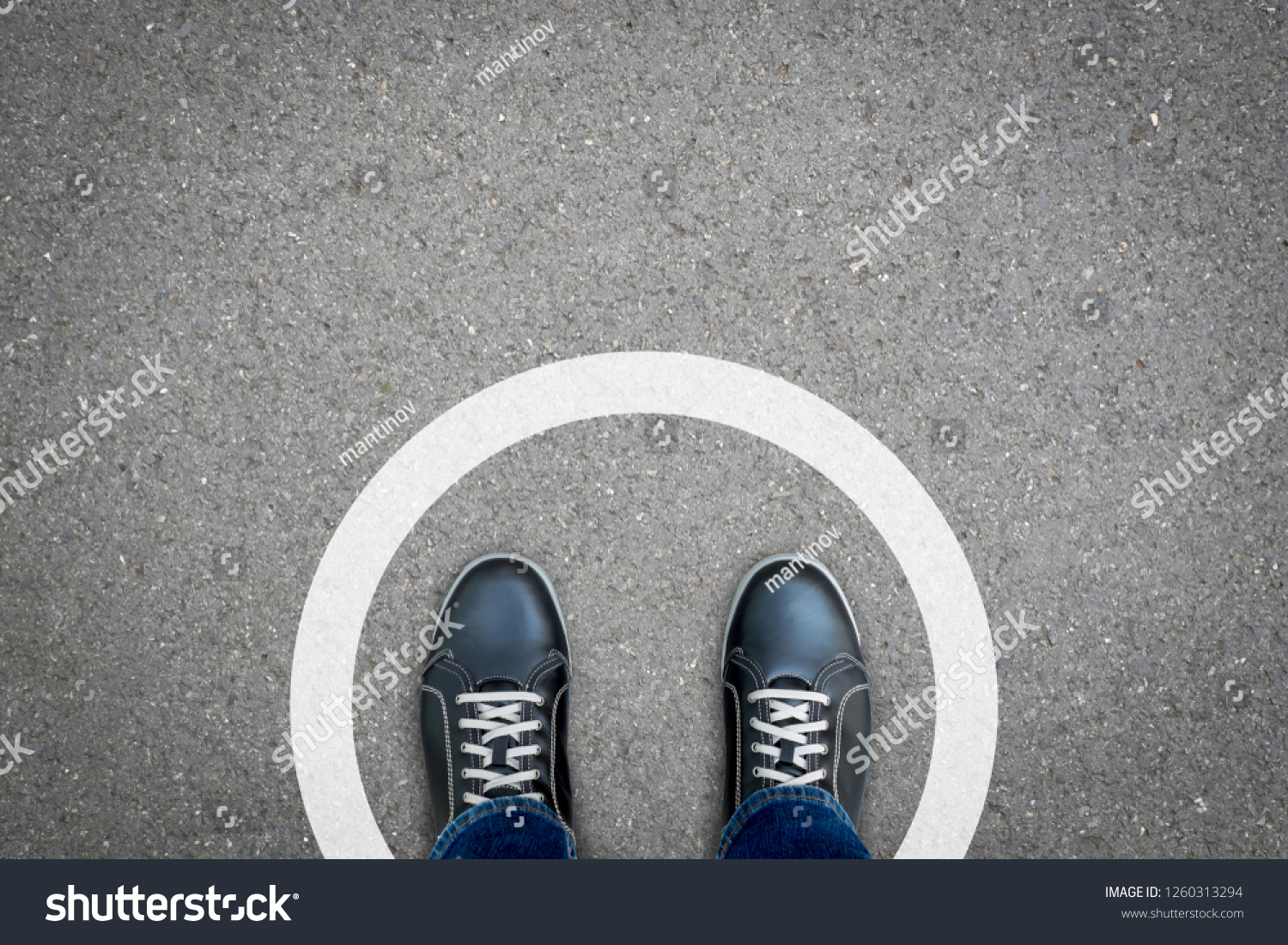 Black shoes standing in white circle on the asphalt concrete floor. Concept of limit, boundary, frame, etc. #1260313294