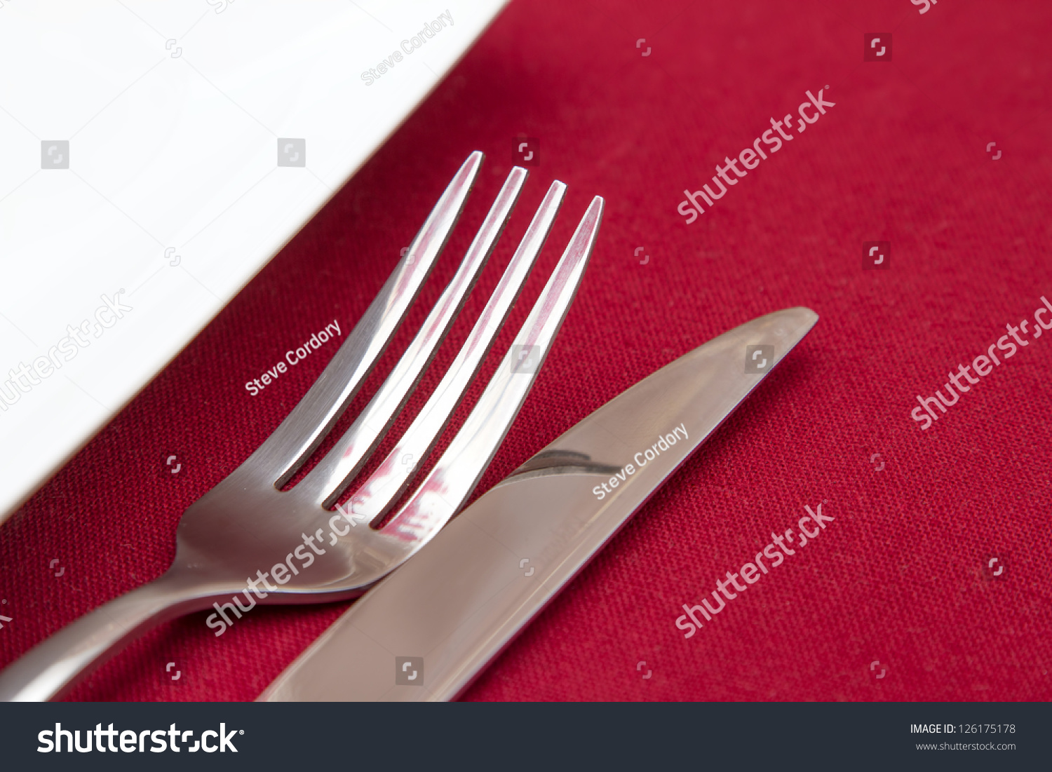 Knife And Fork With White Plate On Red Tablecloth Stock