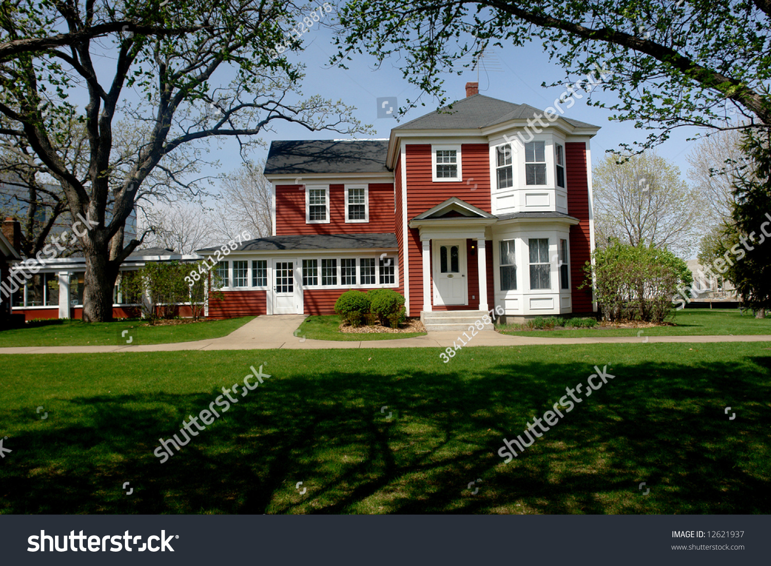A picture of a red farm house with shade in the yard