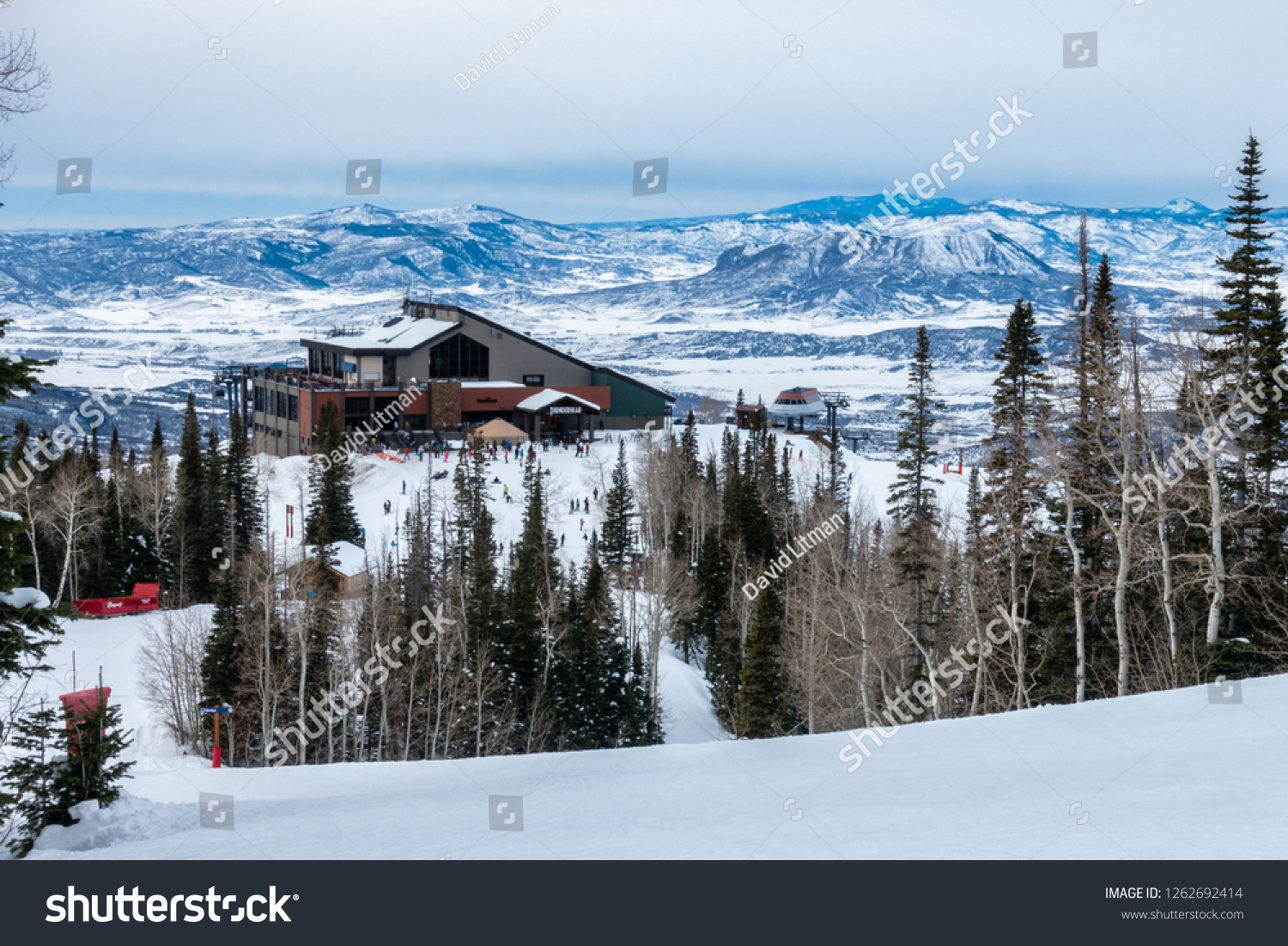 Steamboat Springs, Colorado - December 17, 2018: The Thunderhead Lodge on Mount Werner of the Steamboat Springs Ski Resort can be seen down-slope with a view of the Rocky Mountains in the background.