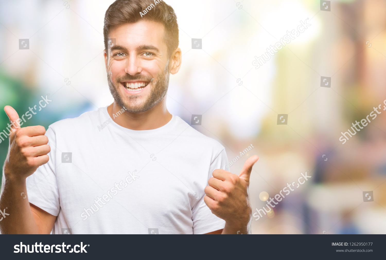 Young handsome man over isolated background success sign doing positive gesture with hand, thumbs up smiling and happy. Looking at the camera with cheerful expression, winner gesture. #1262950177