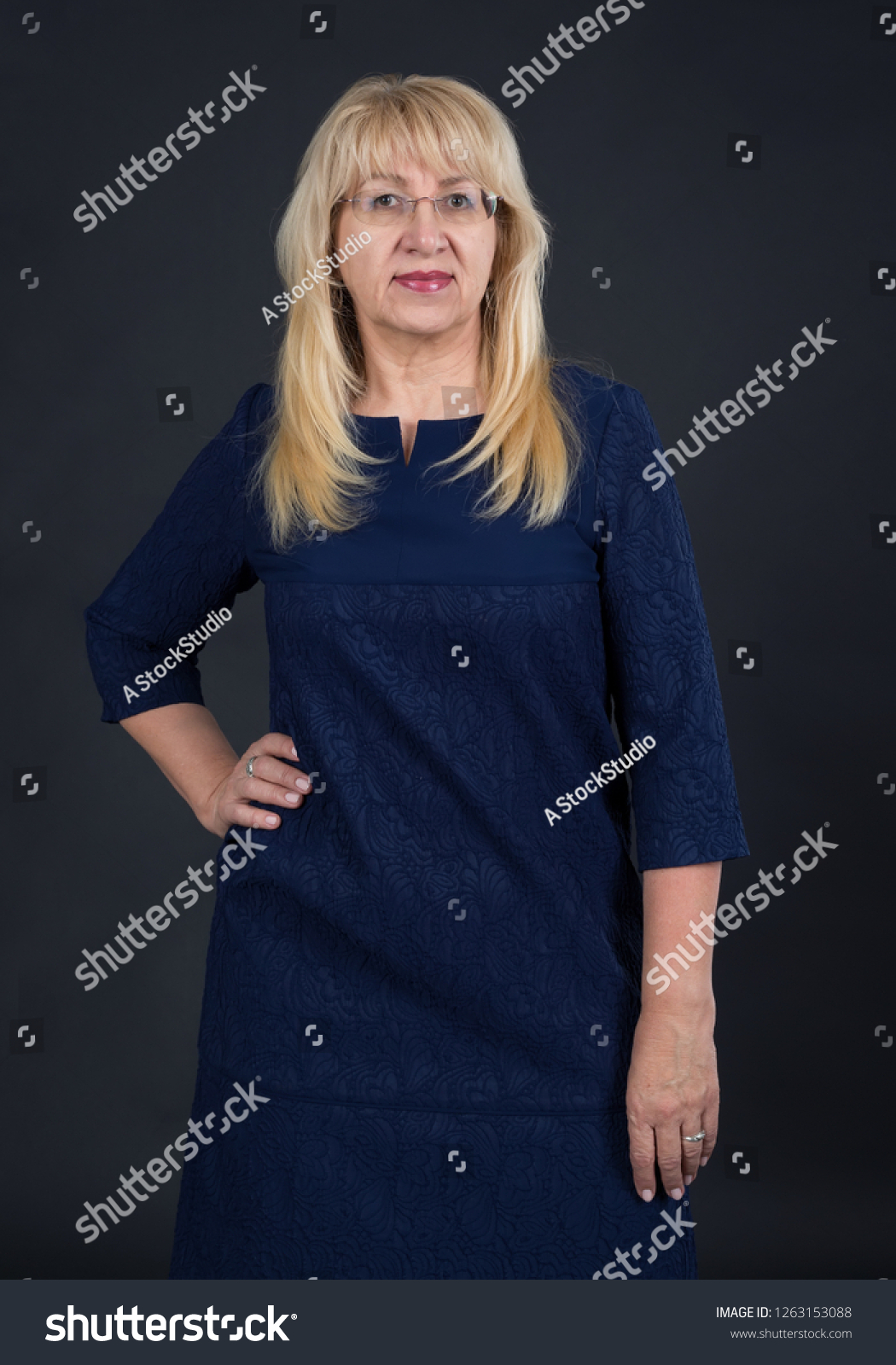 Portrait of senior female in a blue dress. Woman 60 years old on a dark