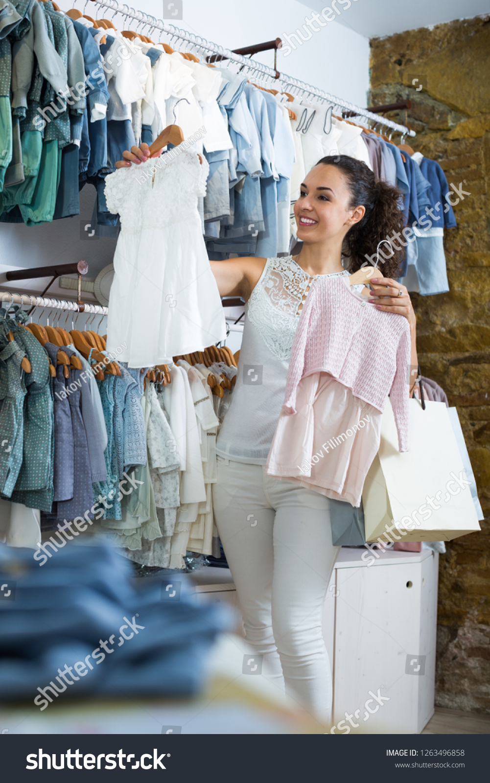45552a695e Young cheerful woman customer holding baby dress in kids apparel boutique