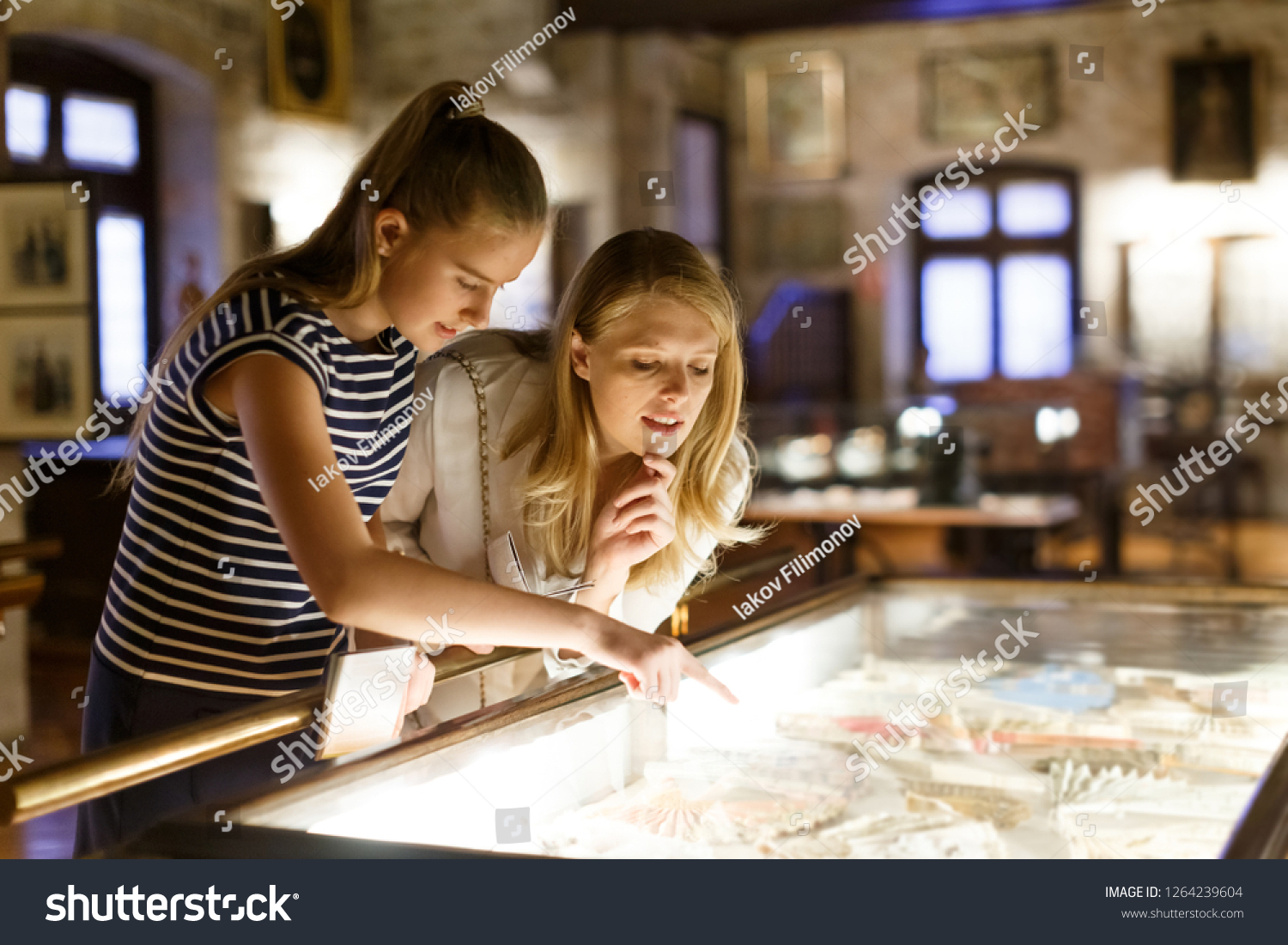 Girl with woman looking with interest at art objects under glass in museum, using guidebook #1264239604
