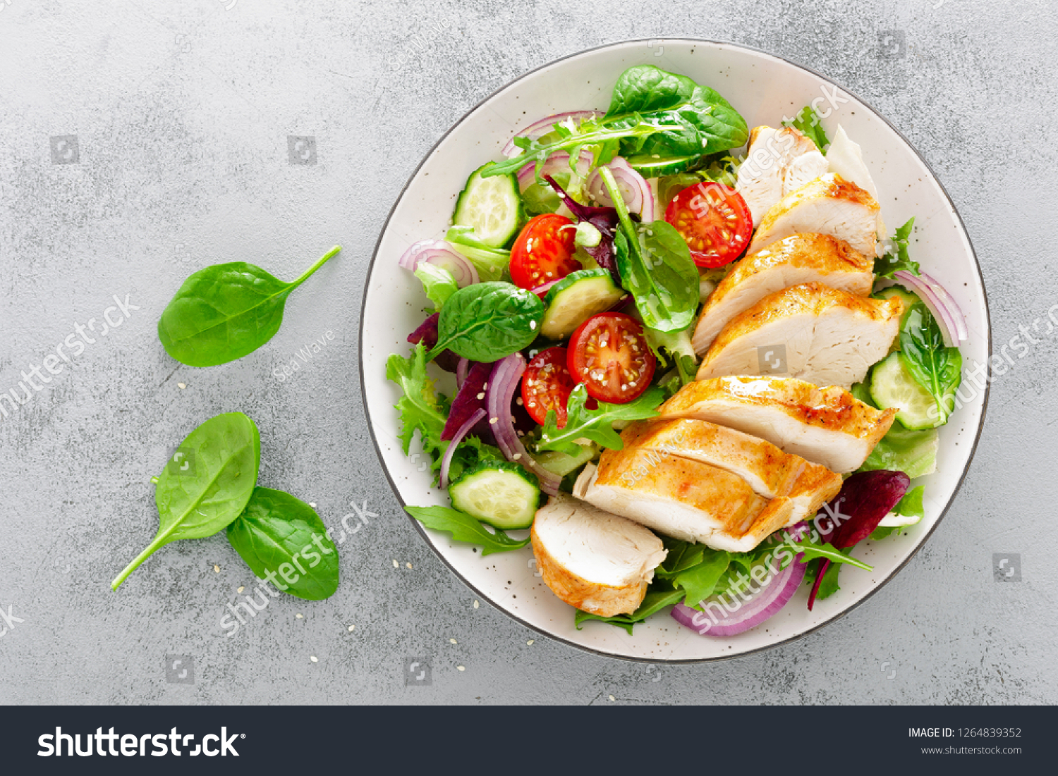 Grilled chicken breast, fillet and fresh vegetable salad of lettuce, arugula, spinach, cucumber and tomato. Healthy lunch menu. Diet food. Top view #1264839352