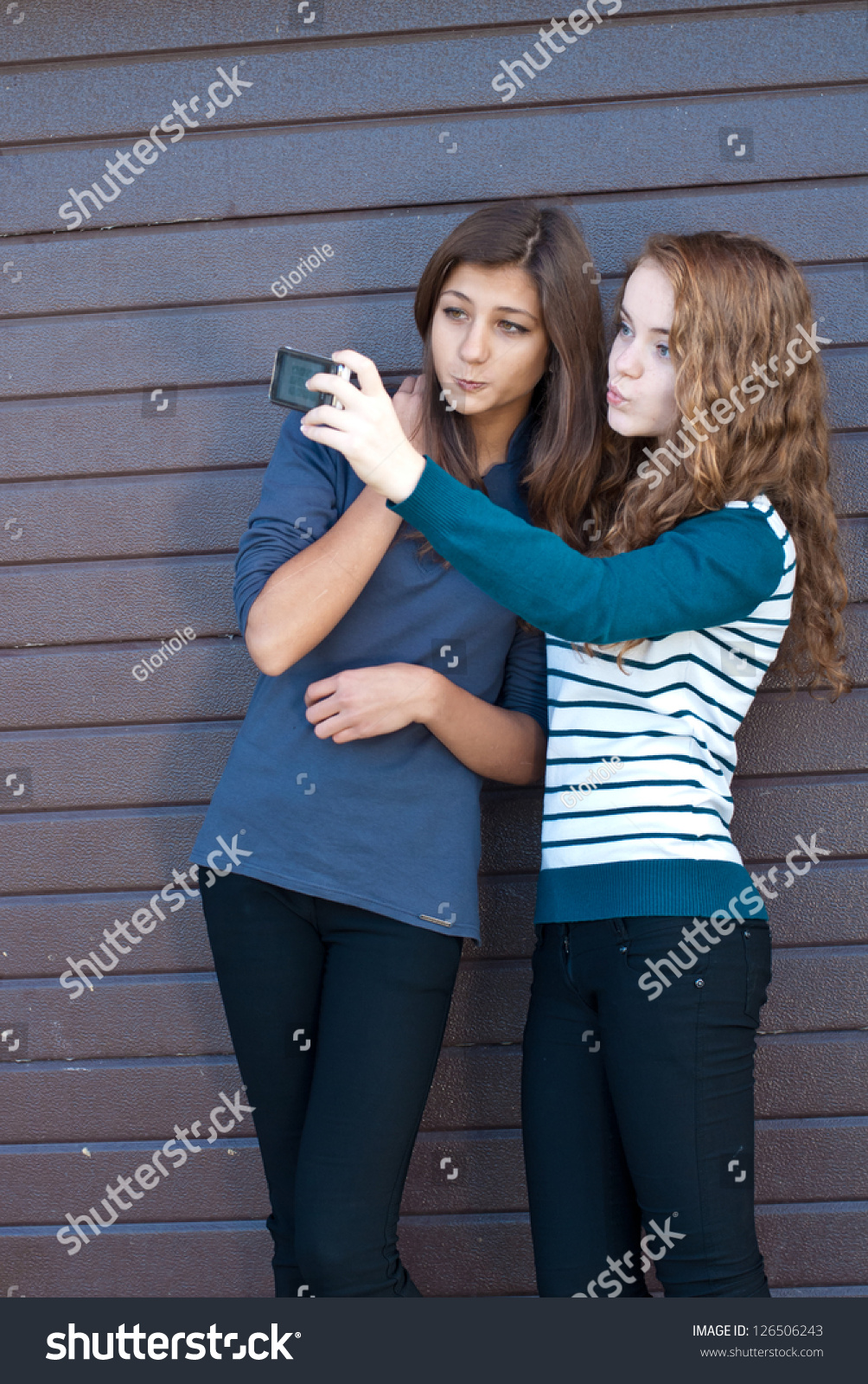 Two teen girls taking selfshot or selfy picture of themselves using tablet  computer