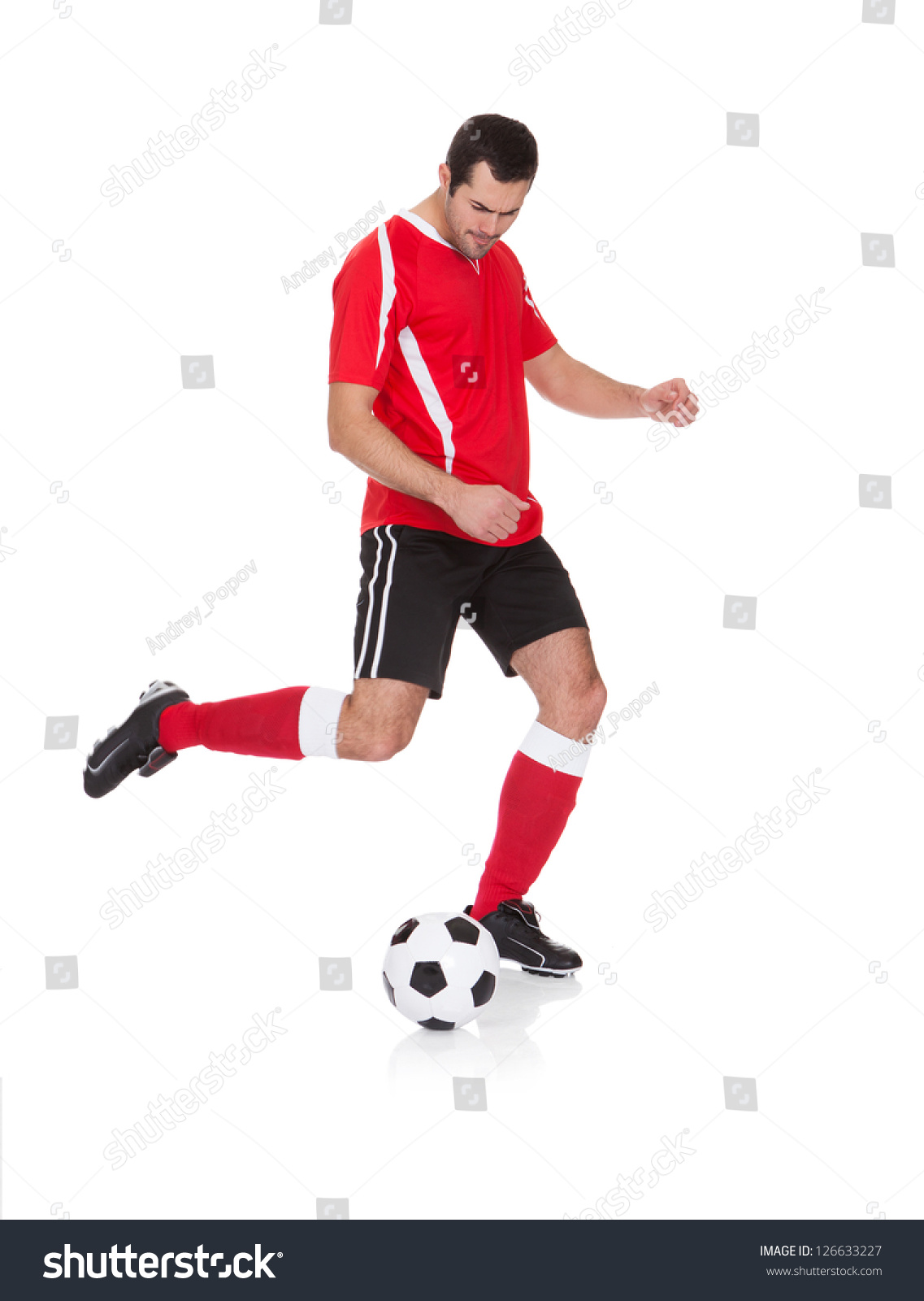 24d7b1a10 Studio shot of a young football player kicking a ball and looking at the  camera isolated on white background