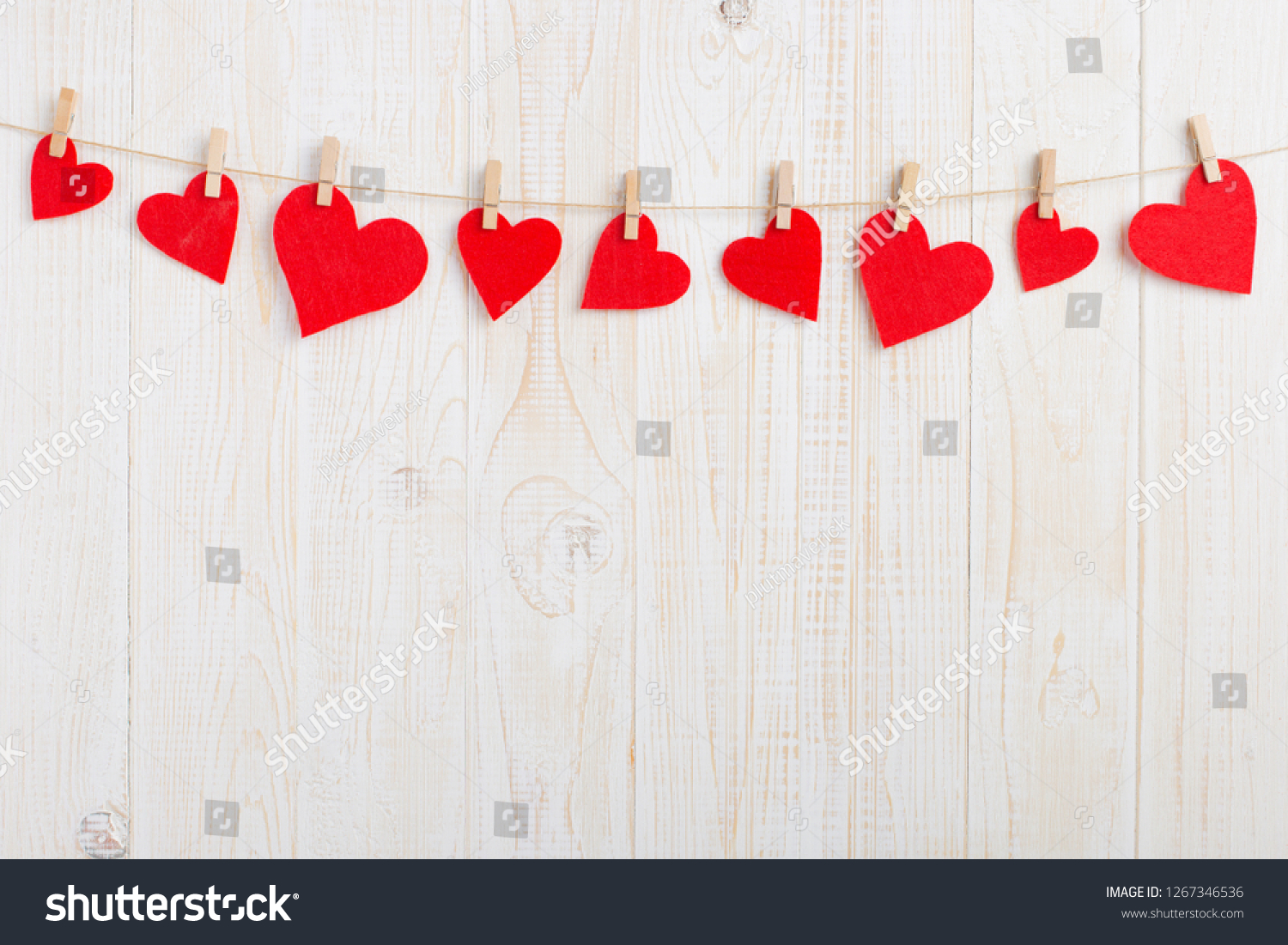 Red hearts on rope with clothespins, on a white wooden background. Place for text, copy space. #1267346536