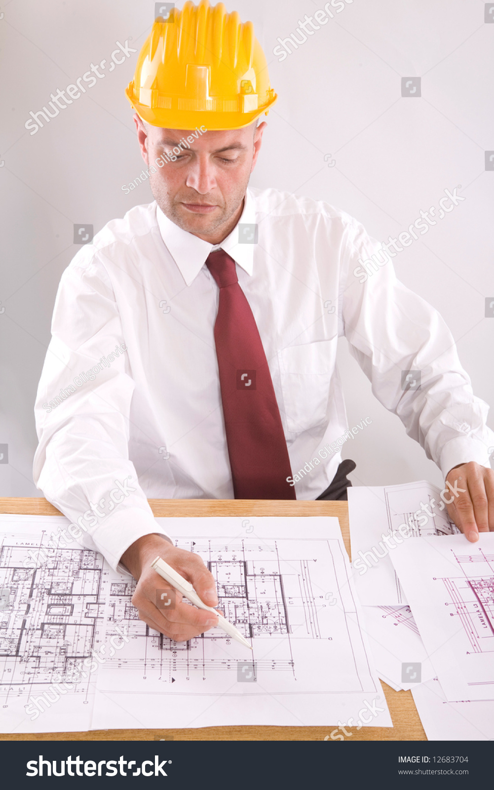 Young architect at work with blueprints stock photo for Architect at work