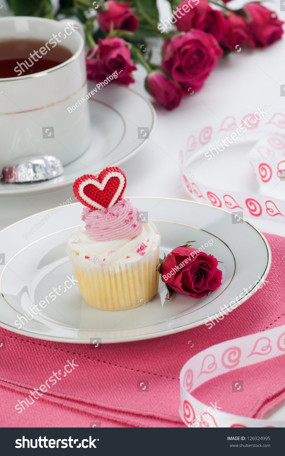 Closeup of cream cupcake on valentine day with heart shaped decoration tea and pink spray roses - Creme decoration cupcake ...