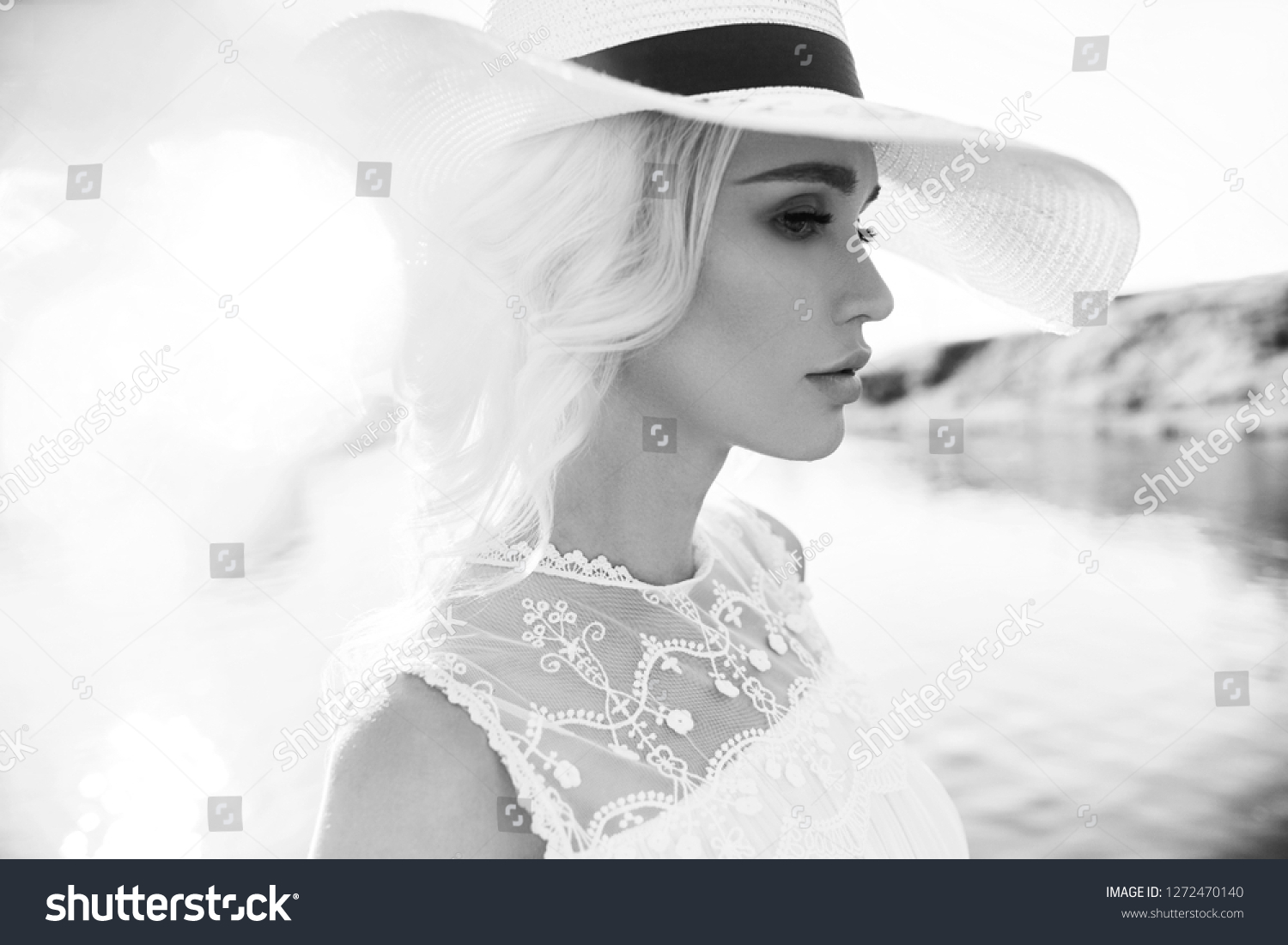 Woman in a big white hat stands near the sea, a blonde in a hat looking at the lake, summer vacation travel and vacation. Sun rays at sunset #1272470140