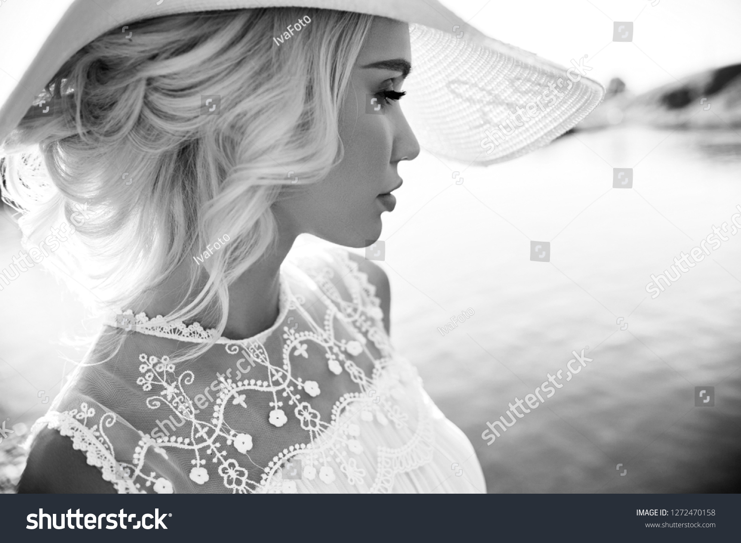 Woman in a big white hat stands near the sea, a blonde in a hat looking at the lake, summer vacation travel and vacation. Sun rays at sunset #1272470158