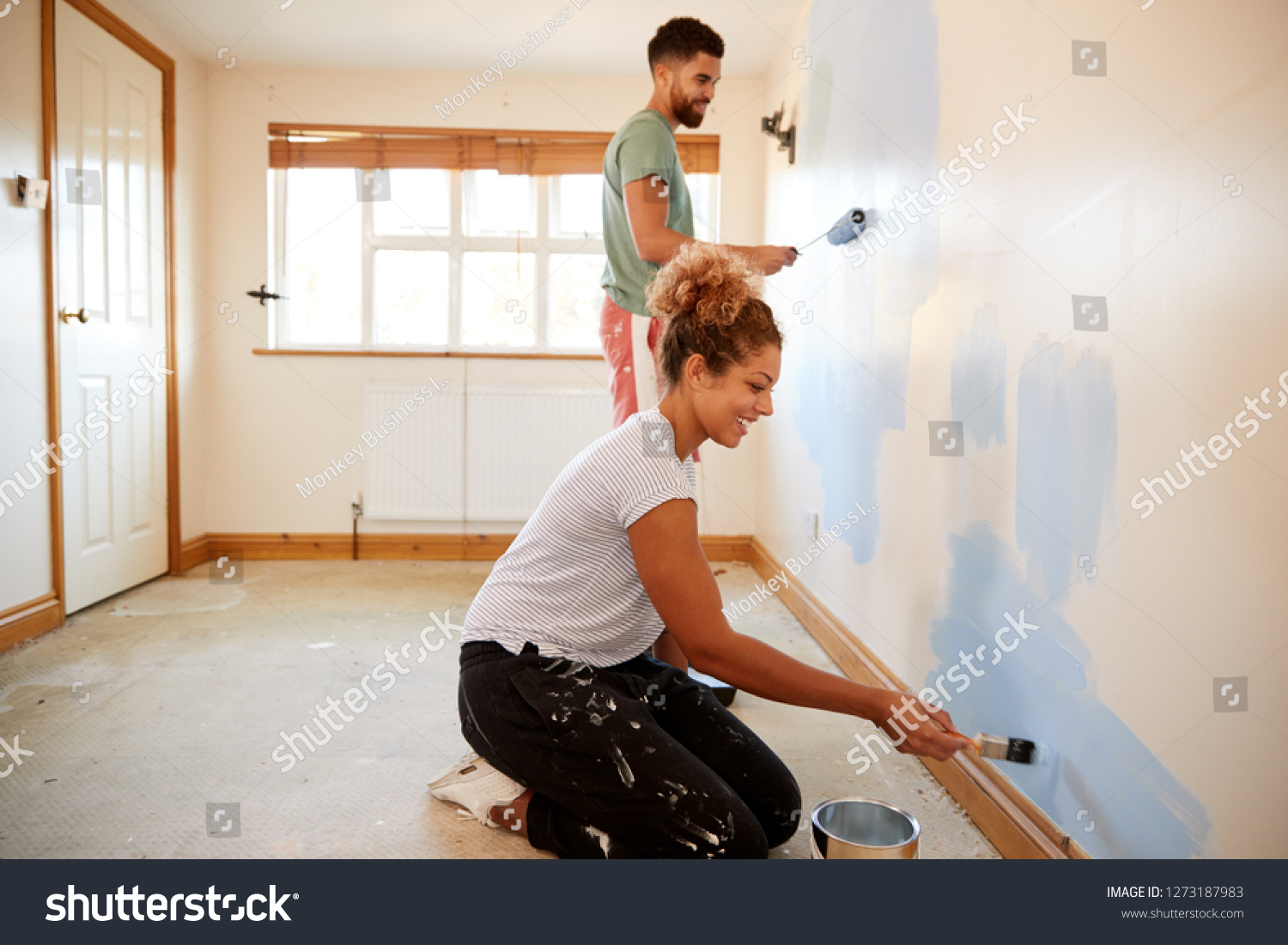 Couple Decorating Room In New Home Painting Wall Together #1273187983