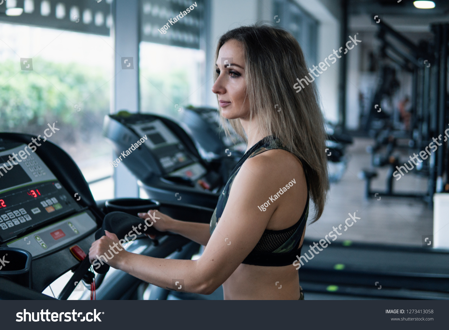 Young fit woman doing running exercise in gym at treadmill speedwalk running road. #1273413058