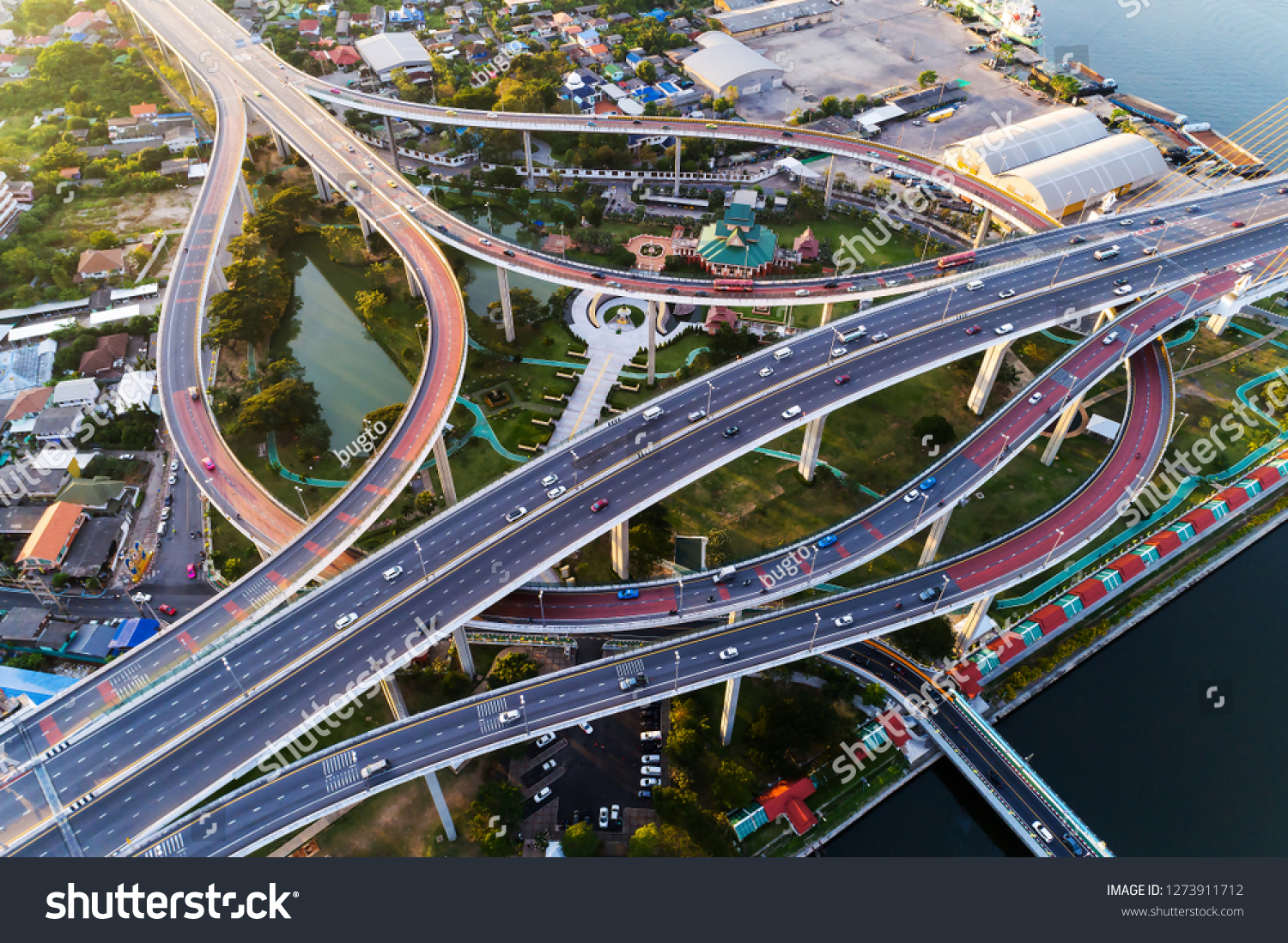 Aerial view shot or intersection of highway road with cityscape background for transportation or traffic. #1273911712