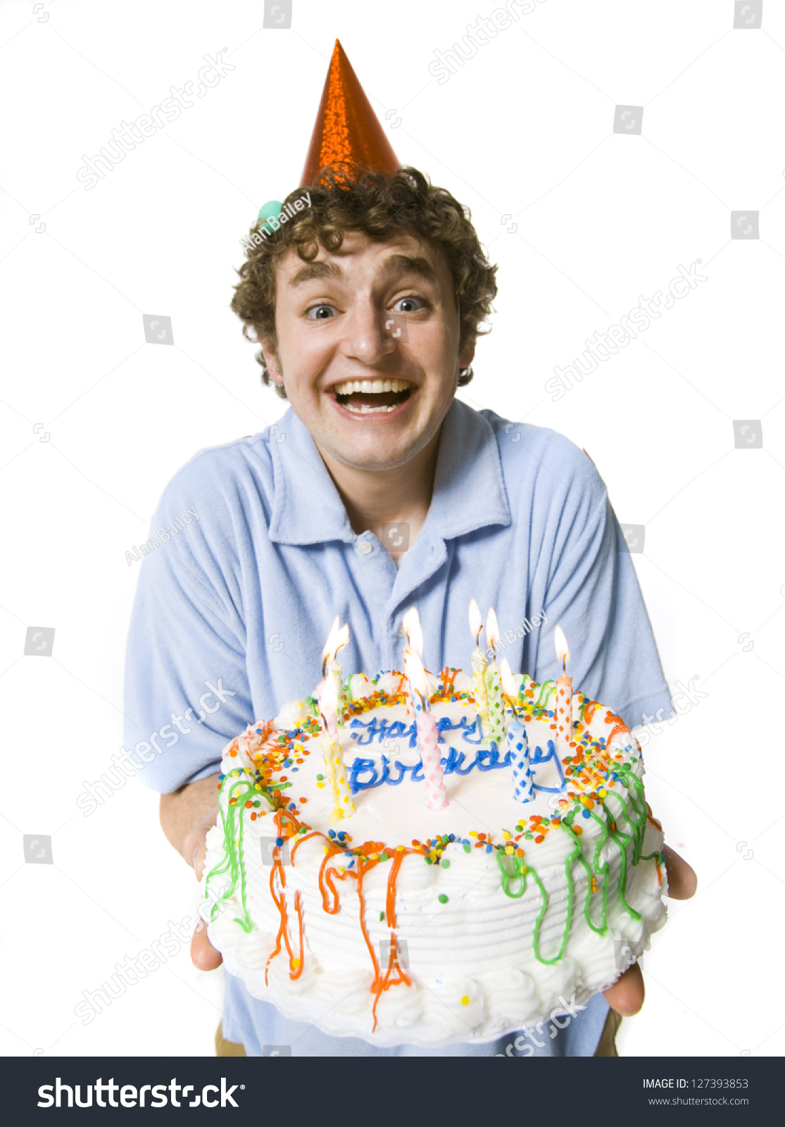 Smiling Young Man In Party Hat Holding A Birthday Cake Stock Photo ...