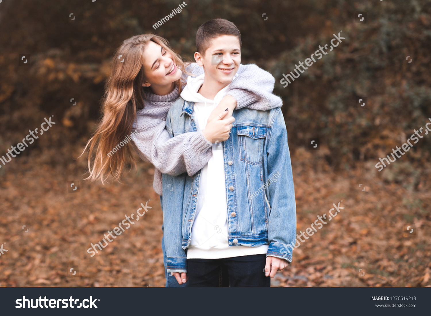 Happy love teen couple 16-17 year old having fun outdoors. Wearing stylish  denim