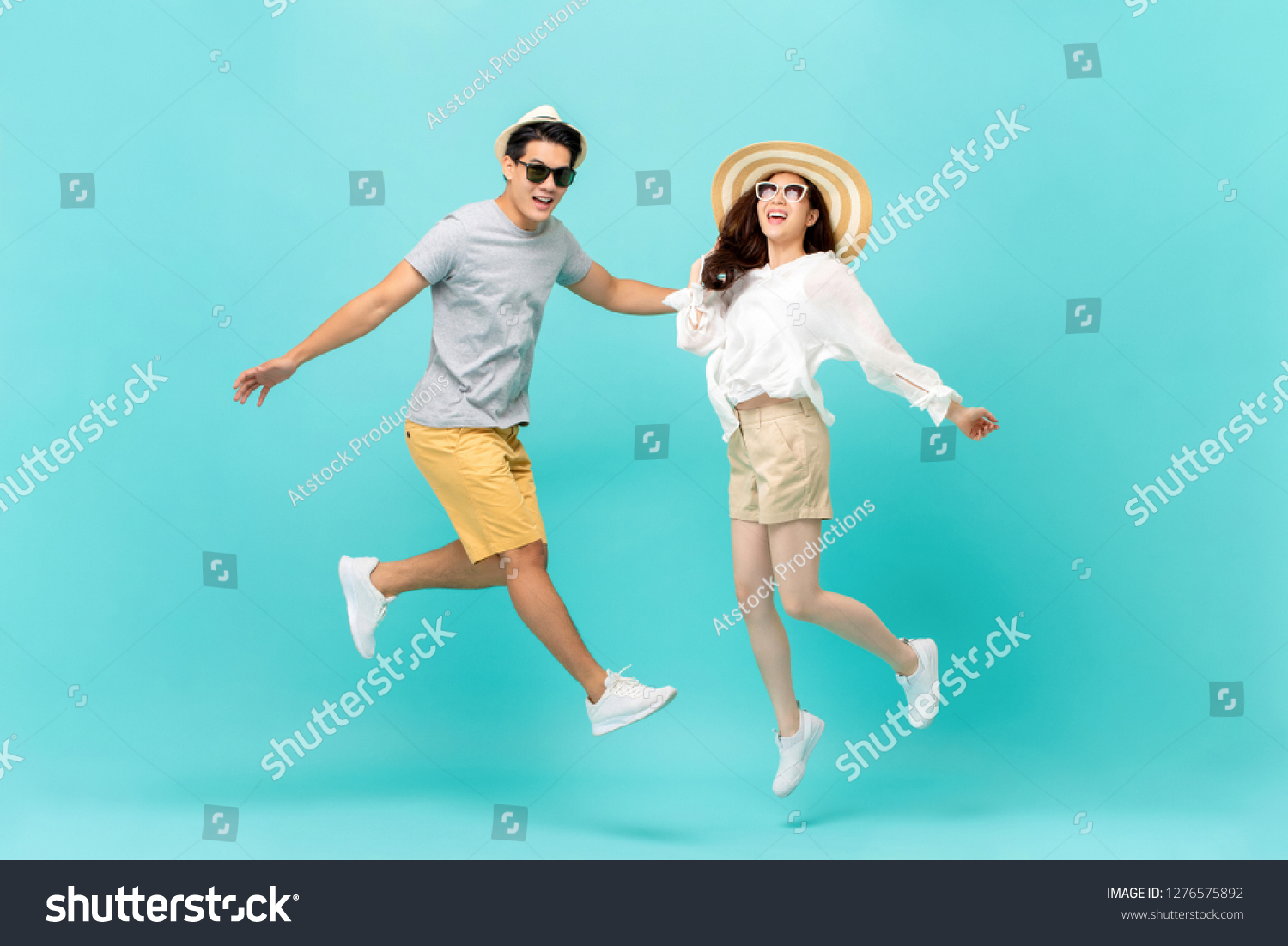 Playful energetic Asian couple in summer beach casual clothes jumping isolated on light blue background studio shot #1276575892