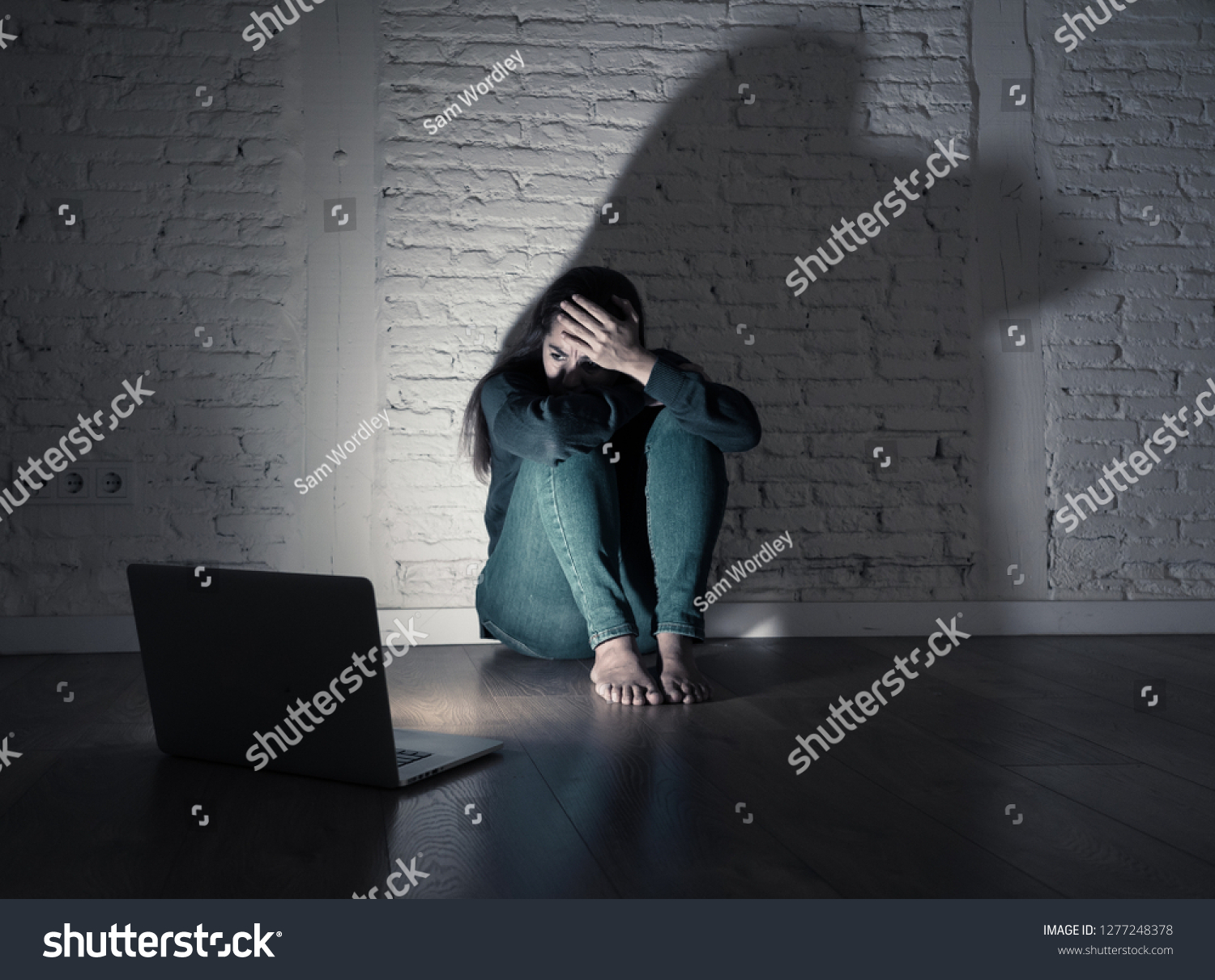 Sad and scared female Young woman with computer laptop suffering cyberbullying and harassment being online abused by stalker or gossip feeling desperate and humiliated in cyber bullying concept. #1277248378