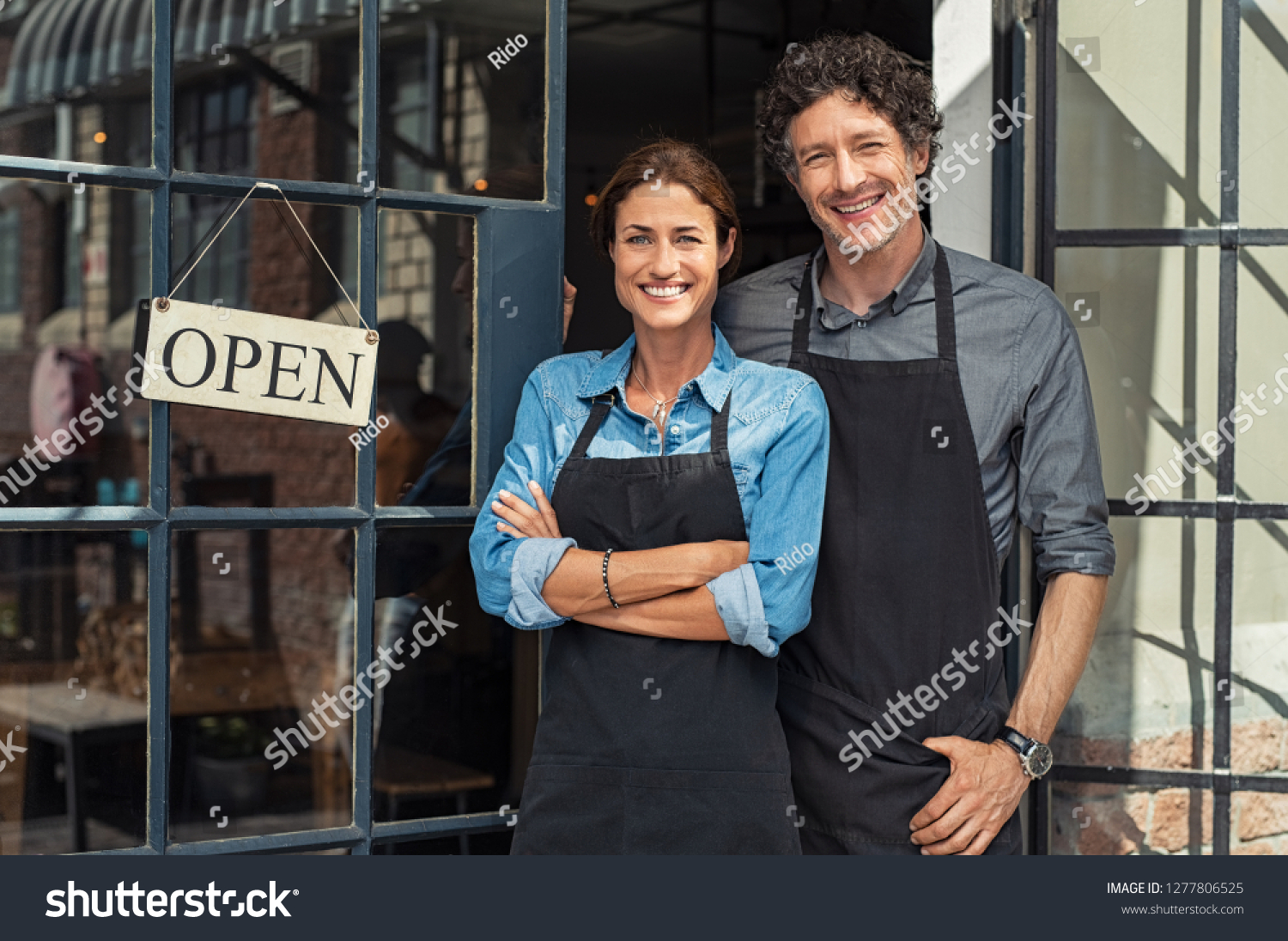 Two cheerful small business owners smiling and looking at camera while standing at entrance door. Happy mature man and mid woman at entrance of newly opened restaurant with open sign board. #1277806525