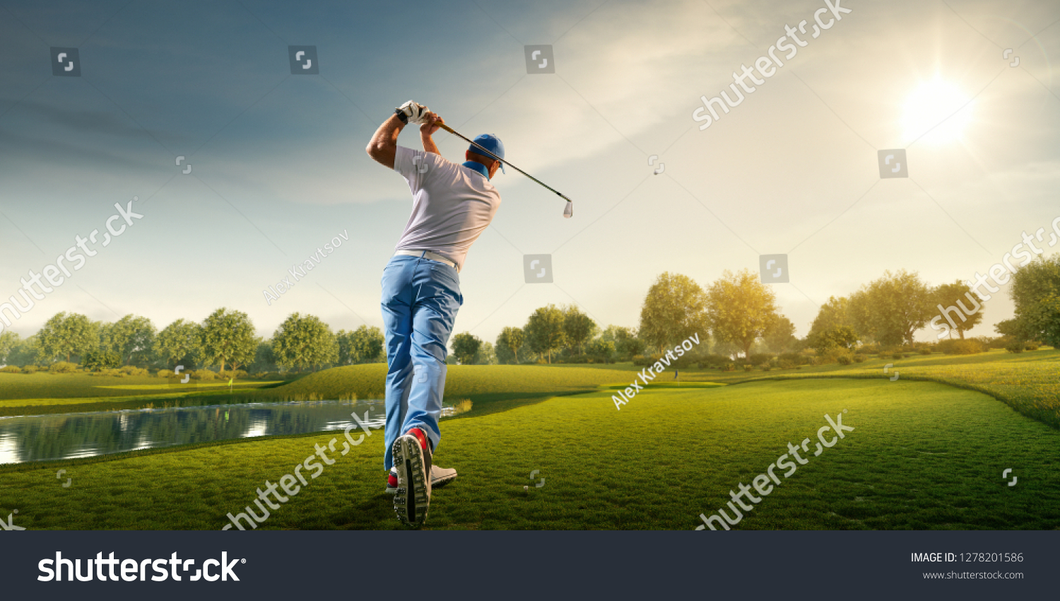 Male golf player on professional golf course. Golfer with golf club taking a shot #1278201586
