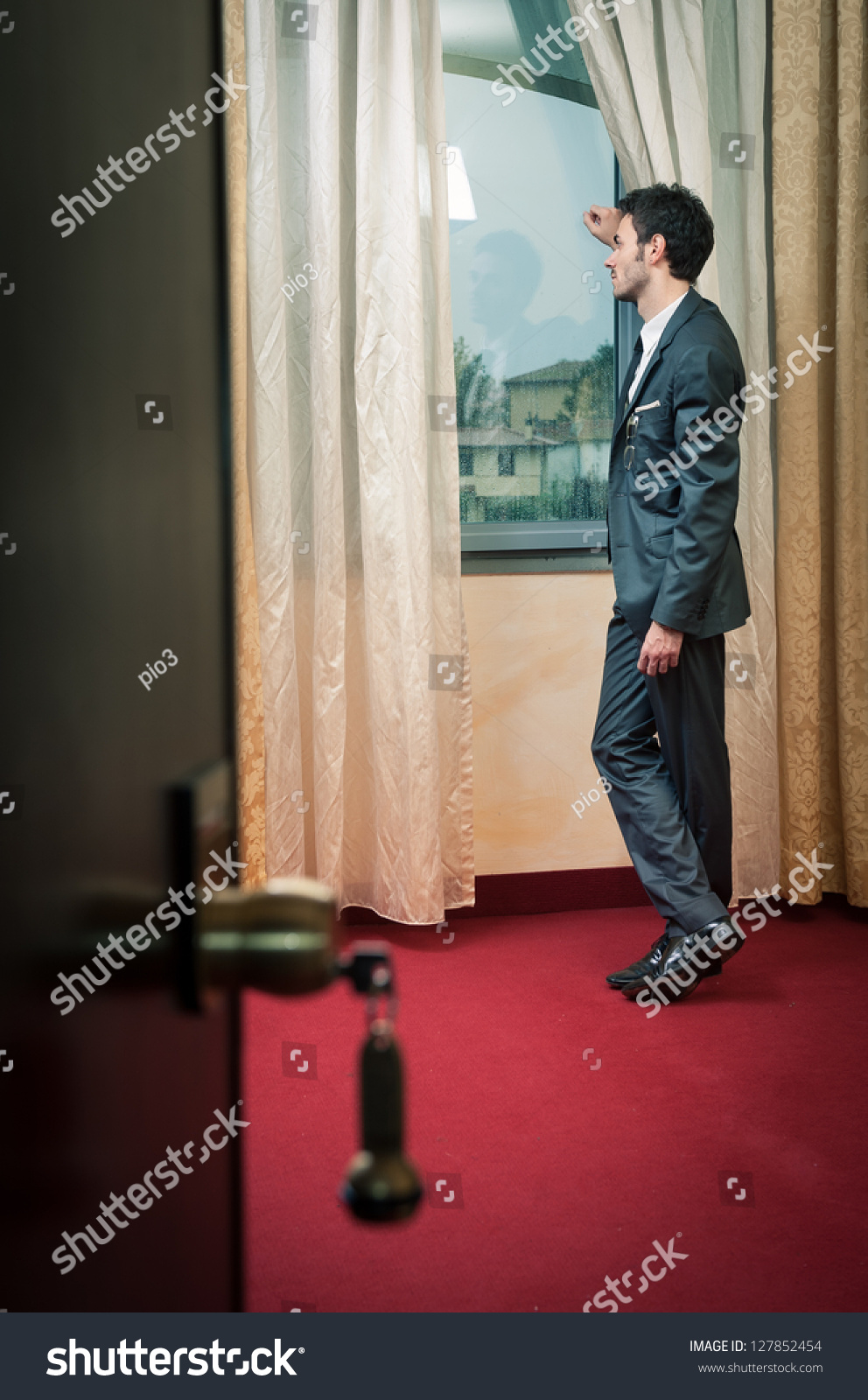 Inside Hotel Room: Lonely Man At The Window Inside Hotel Room. Stock Photo