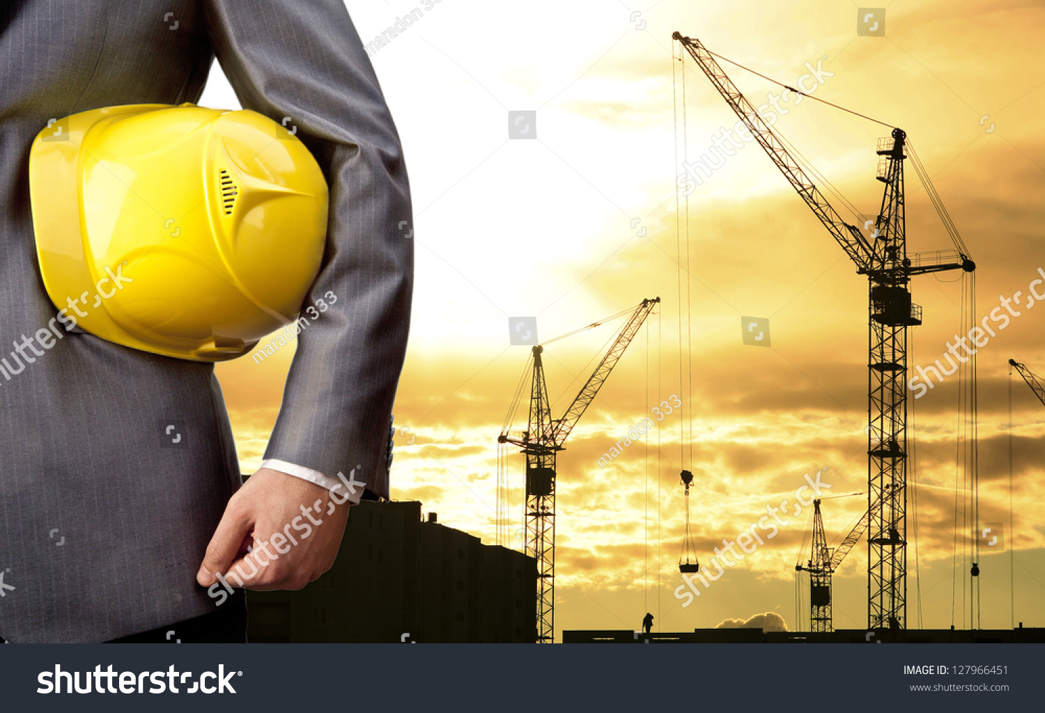 engineer holding yellow helmet for workers security on