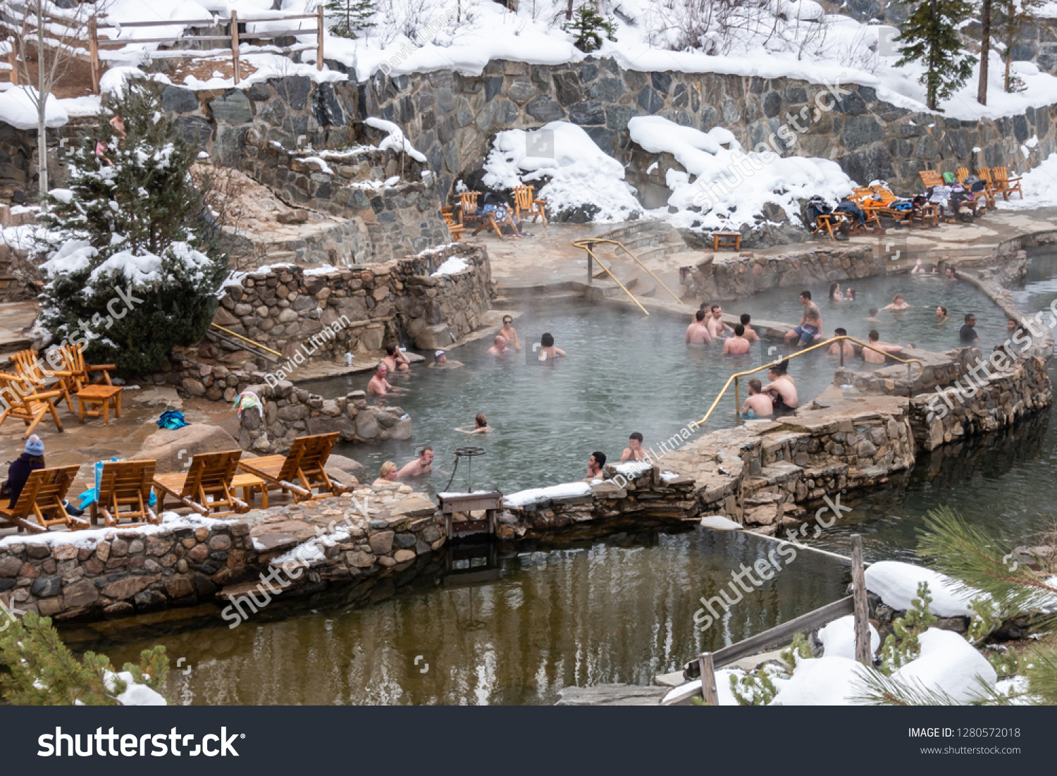 Steamboat Springs, Colorado - December 19, 2018: People enjoy the outdoor Stawberry Park Hot Springs, to relax in the hot water after a day of skiing on the nearby slopes of Mount Werner.