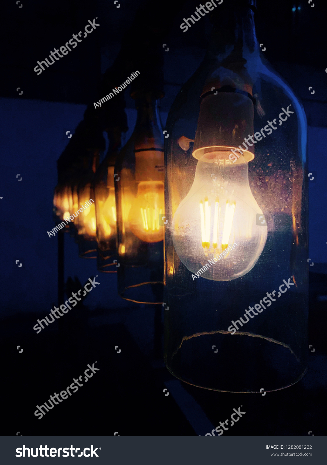 Set of hanging white and orange glass bulb lights in a dark room