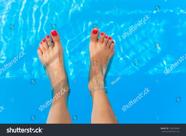 female feet splashing swimming pool stock photo (royalty free