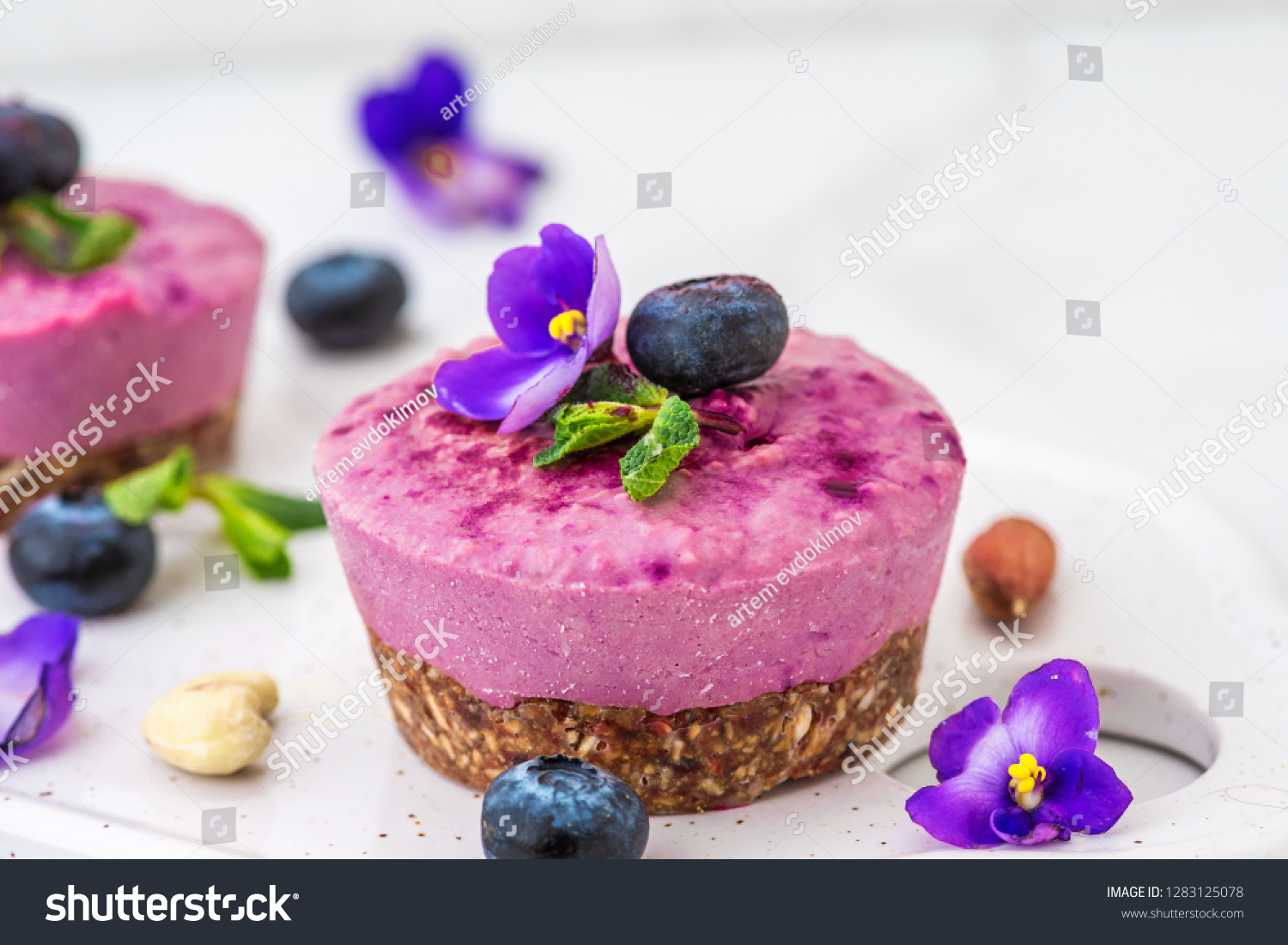 blueberry and acai vegan cashew cakes with fresh berries, edible flowers, mint, nuts. healthy vegan food concept. close up #1283125078