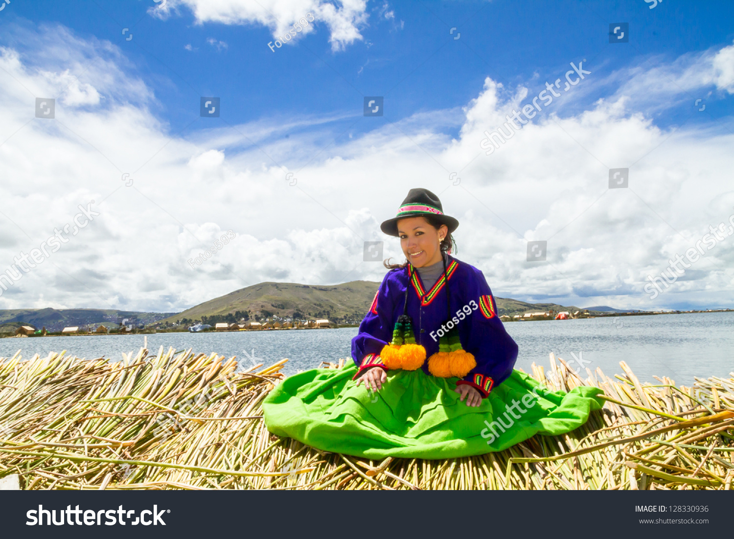 Young local girl on a floating Uros island standing in front of her home, lake Titicaca #128330936