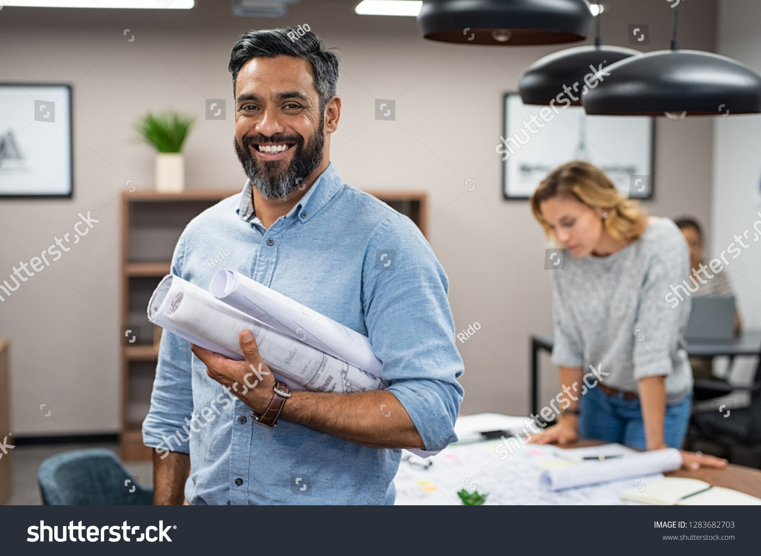Portrait of multiethnic architect with blueprints in creative office. Mature middle eastern contractor holding roll of architectural projects while looking at camera. Happy latin man in casual. #1283682703