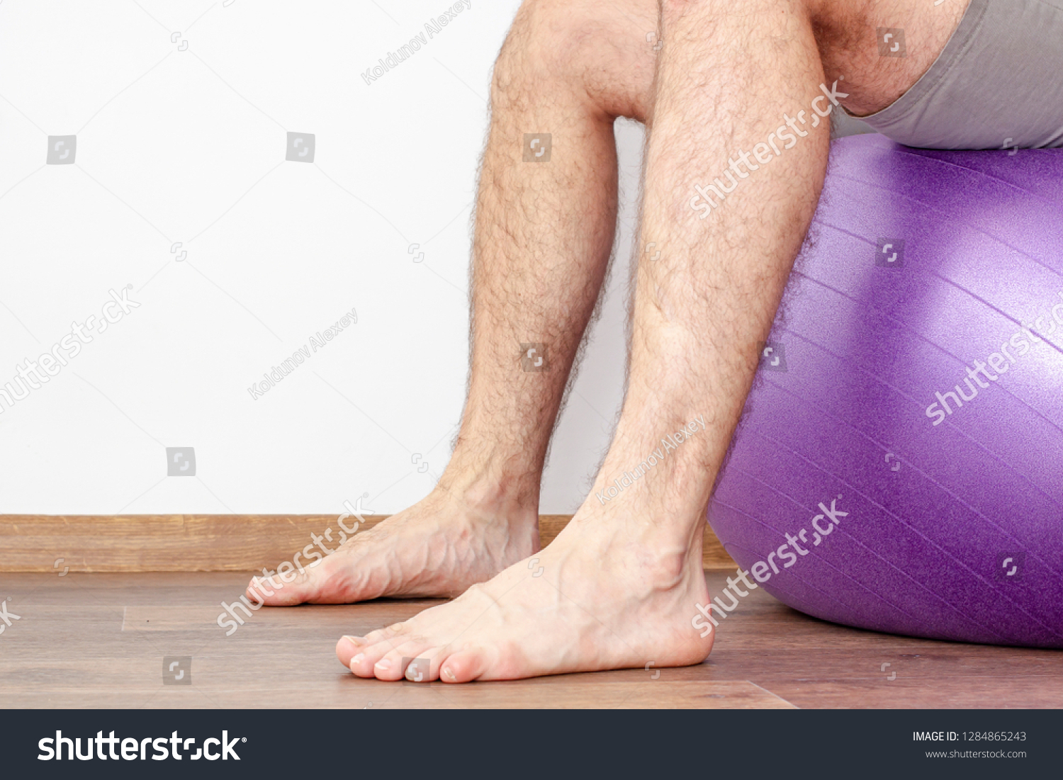 Man with hairy legs sitting on a fitness ball. Close-up. #1284865243