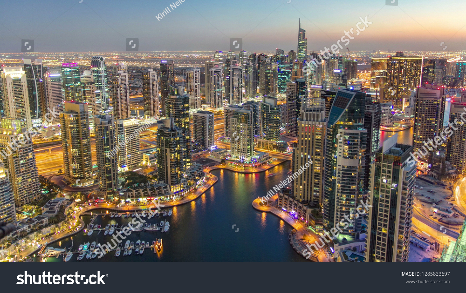 Dubai Marina with yachts in harbor and modern towers from top of skyscraper transition from day to night , Glittering lights and tallest skyscrapers during a clear evening with Blue sky.  #1285833697