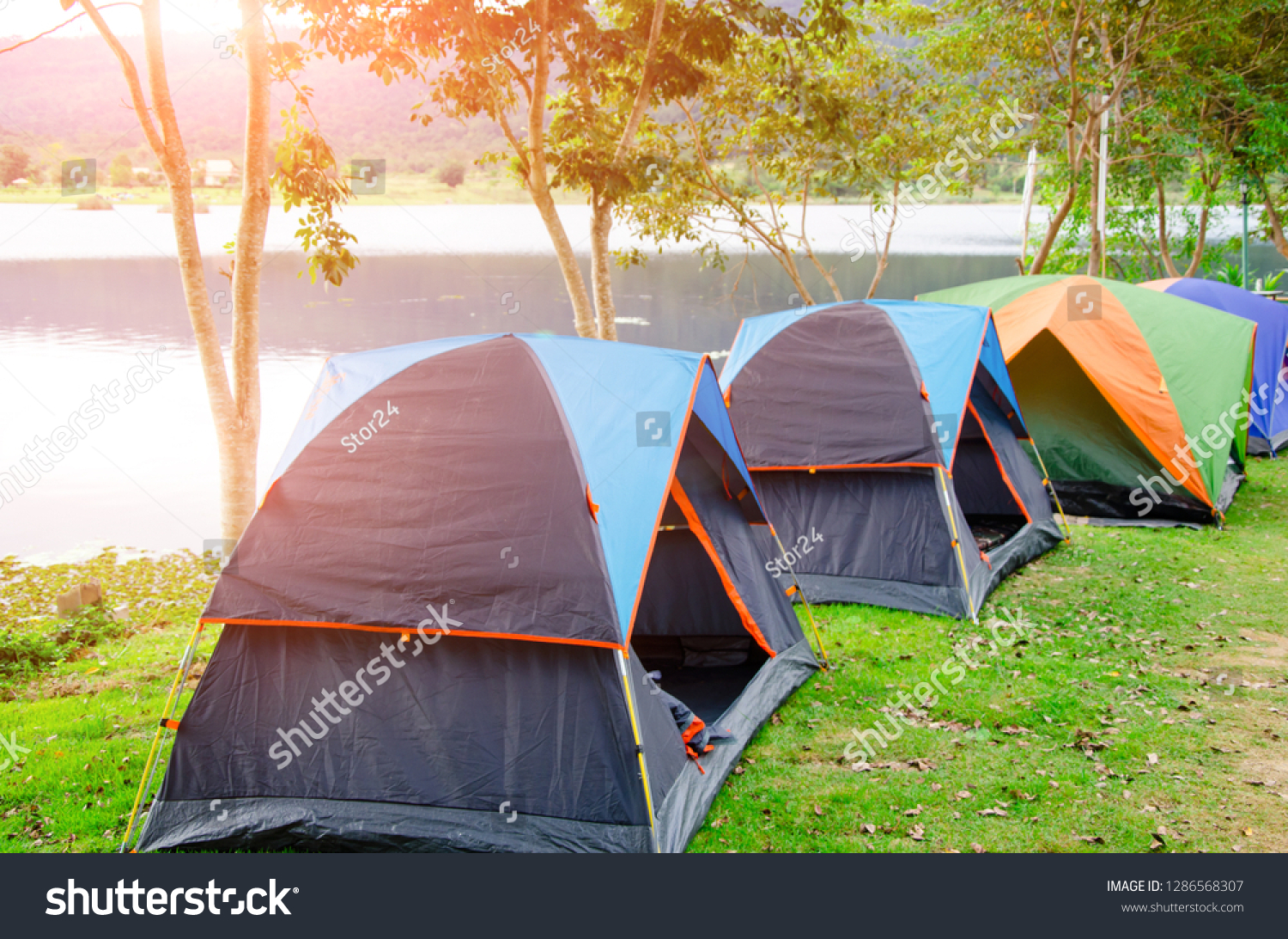 Camping tents in forest near lake side in sunrise with sunlight on the morning.Tourist camp outdoor is the travel to experience close to nature #1286568307
