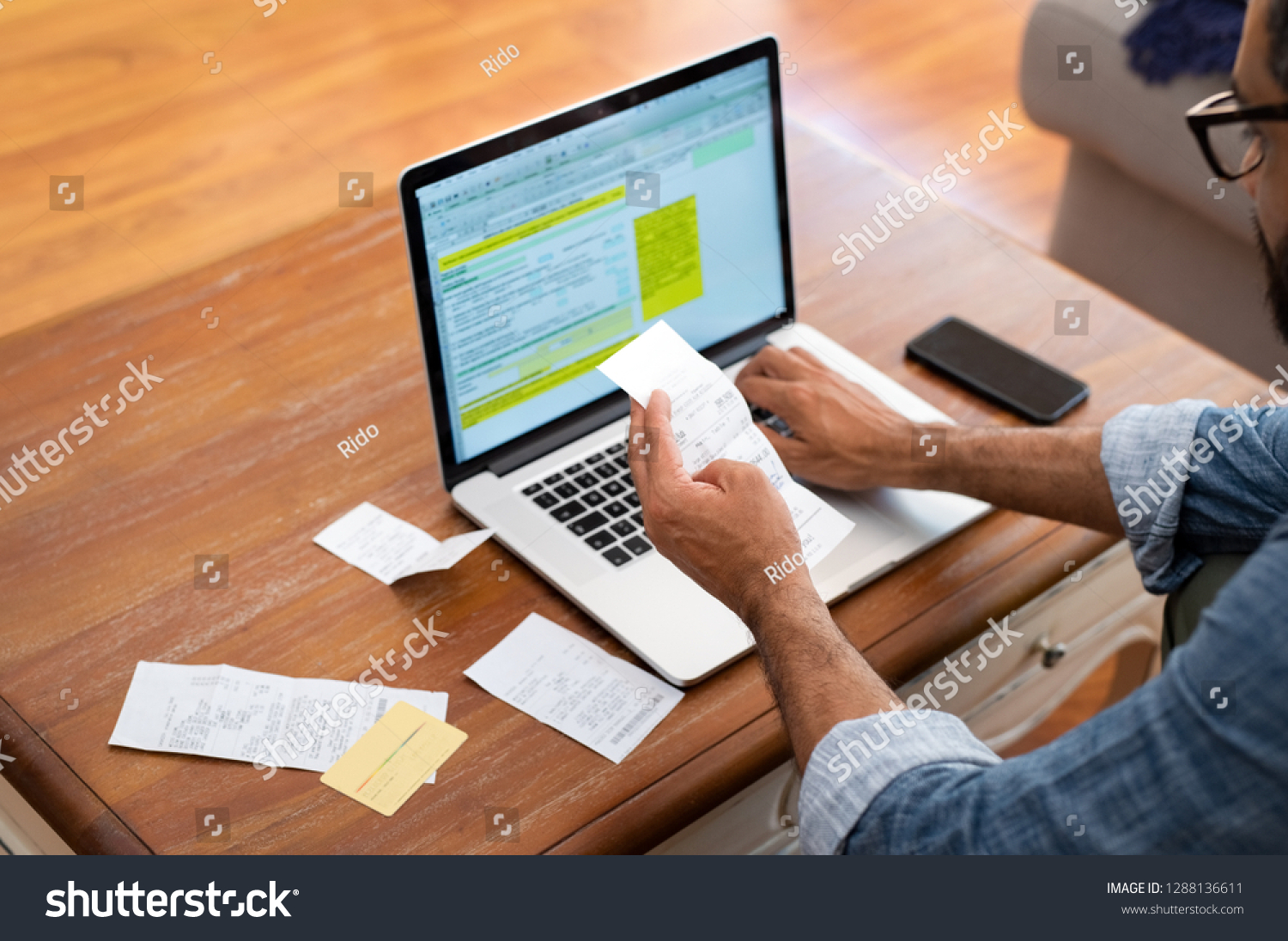 Hands of businessman analyzing invoice on laptop while checking bills. Rear view of latin man checking invoice while matching them on computer. Closeup of man hands calculating financial expenses. #1288136611