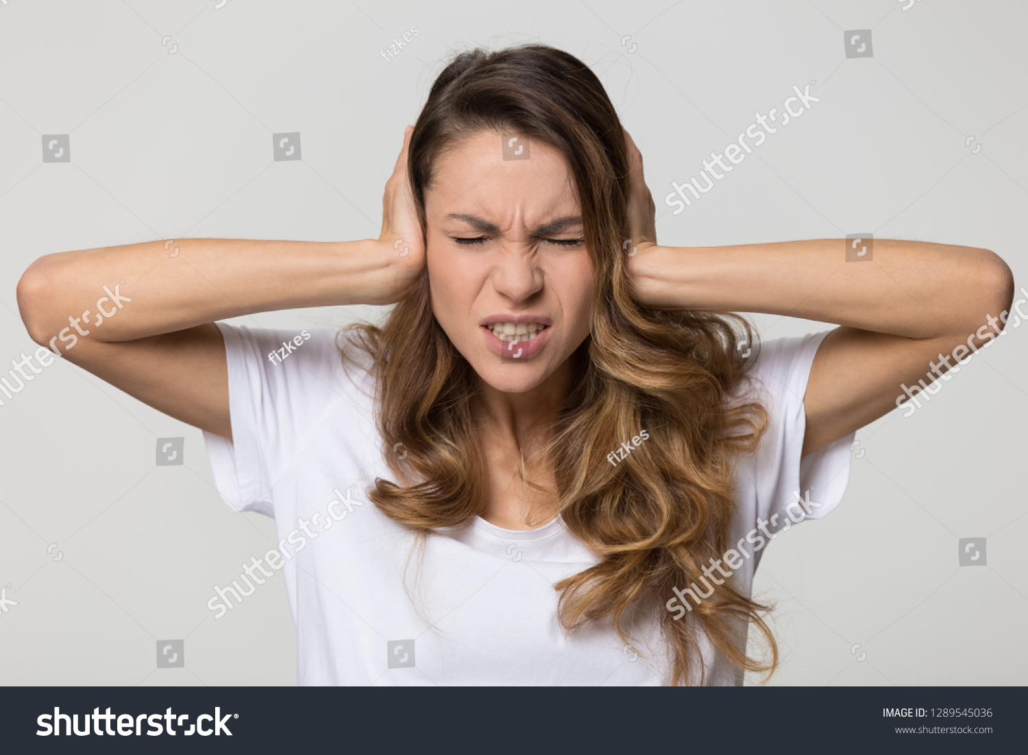 Annoyed stressed woman cover ears feel hurt ear ache pain otitis suffer from loud noise sound headache, irritated stubborn girl deaf hear not listen to noisy music isolated on white studio background #1289545036