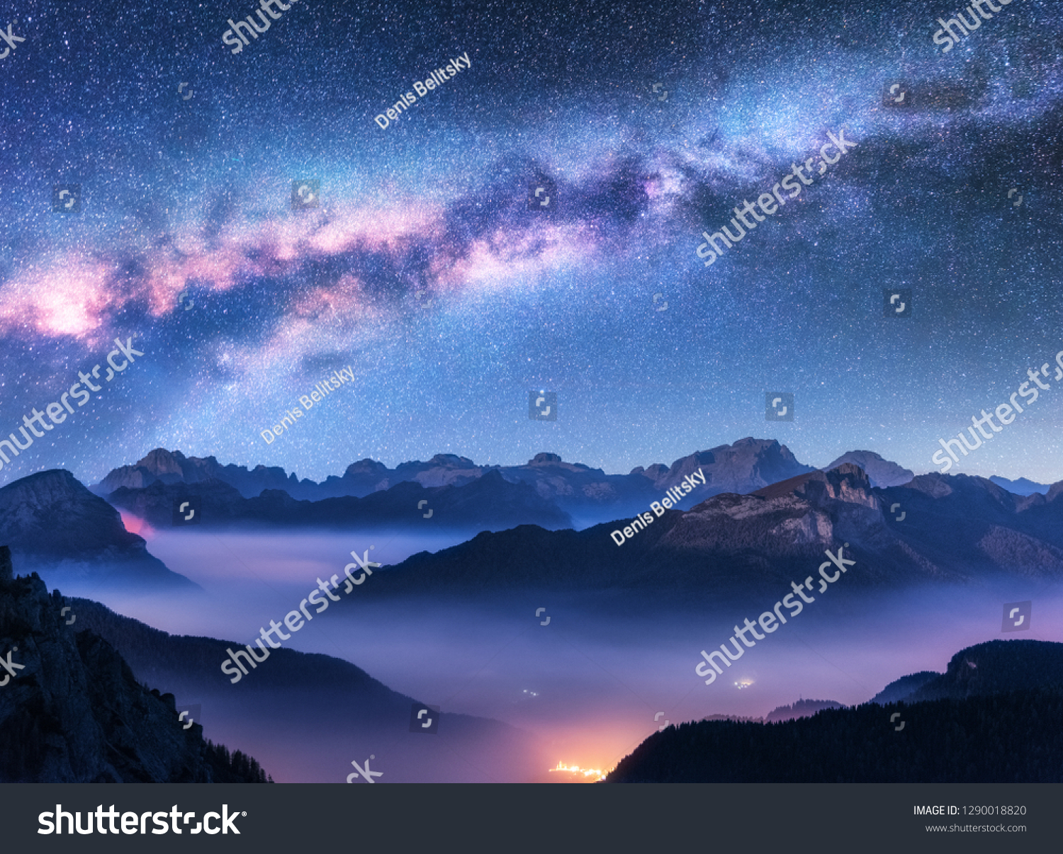 Milky Way above mountains in fog at night in autumn. Landscape with alpine mountain valley, low clouds, purple starry sky with milky way, city illumination. Aerial. Passo Giau, Dolomites, Italy. Space #1290018820