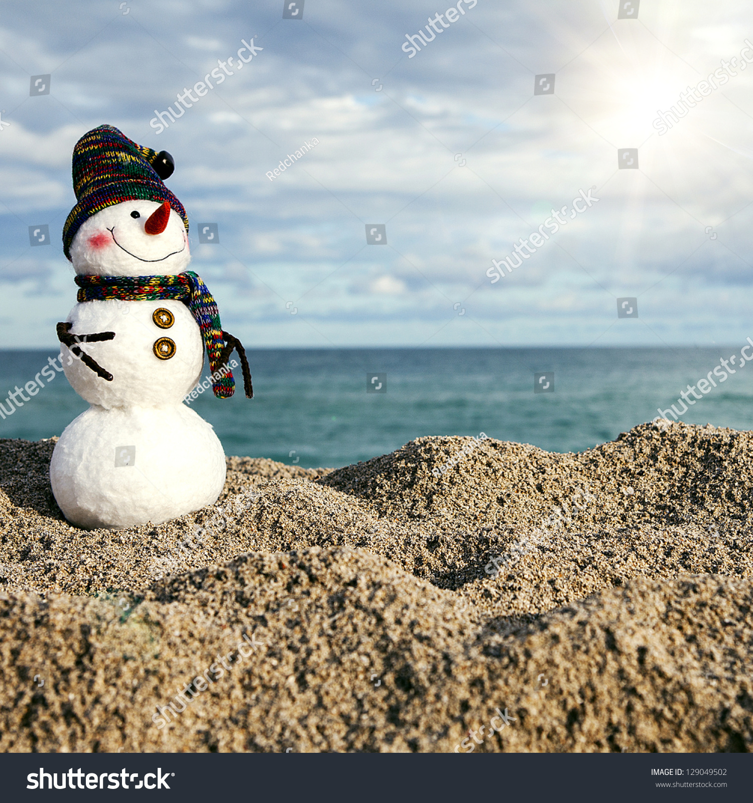 Smiling snowman on sea beach holiday stock photo