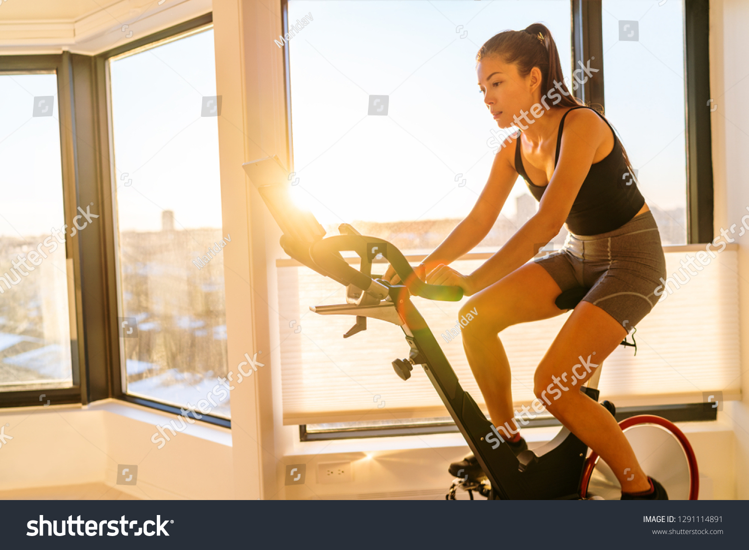 Home fitness workout woman training on smart stationary bike indoors watching screen connected online to live streaming subscription service for biking exercise. Young Asian woman athlete. #1291114891