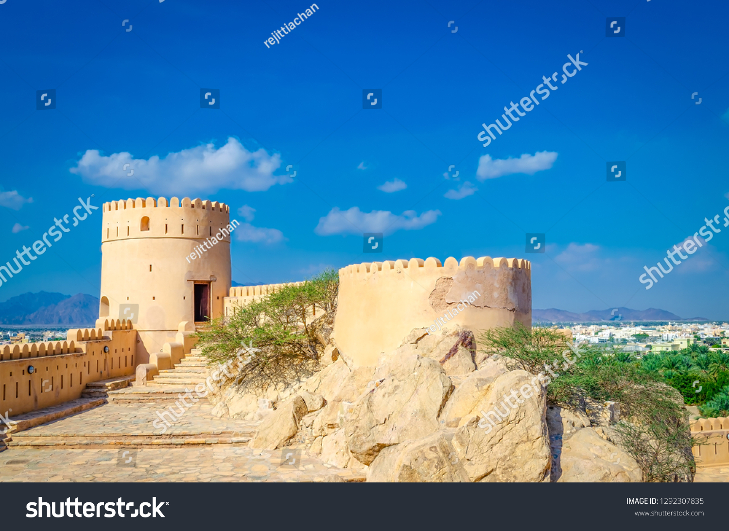 Turret of old, abandoned fort in Nakhal, Muscat, Oman on a clear and bright sunny day. Blue sky with minimal clouds and a desert oasis in the background.